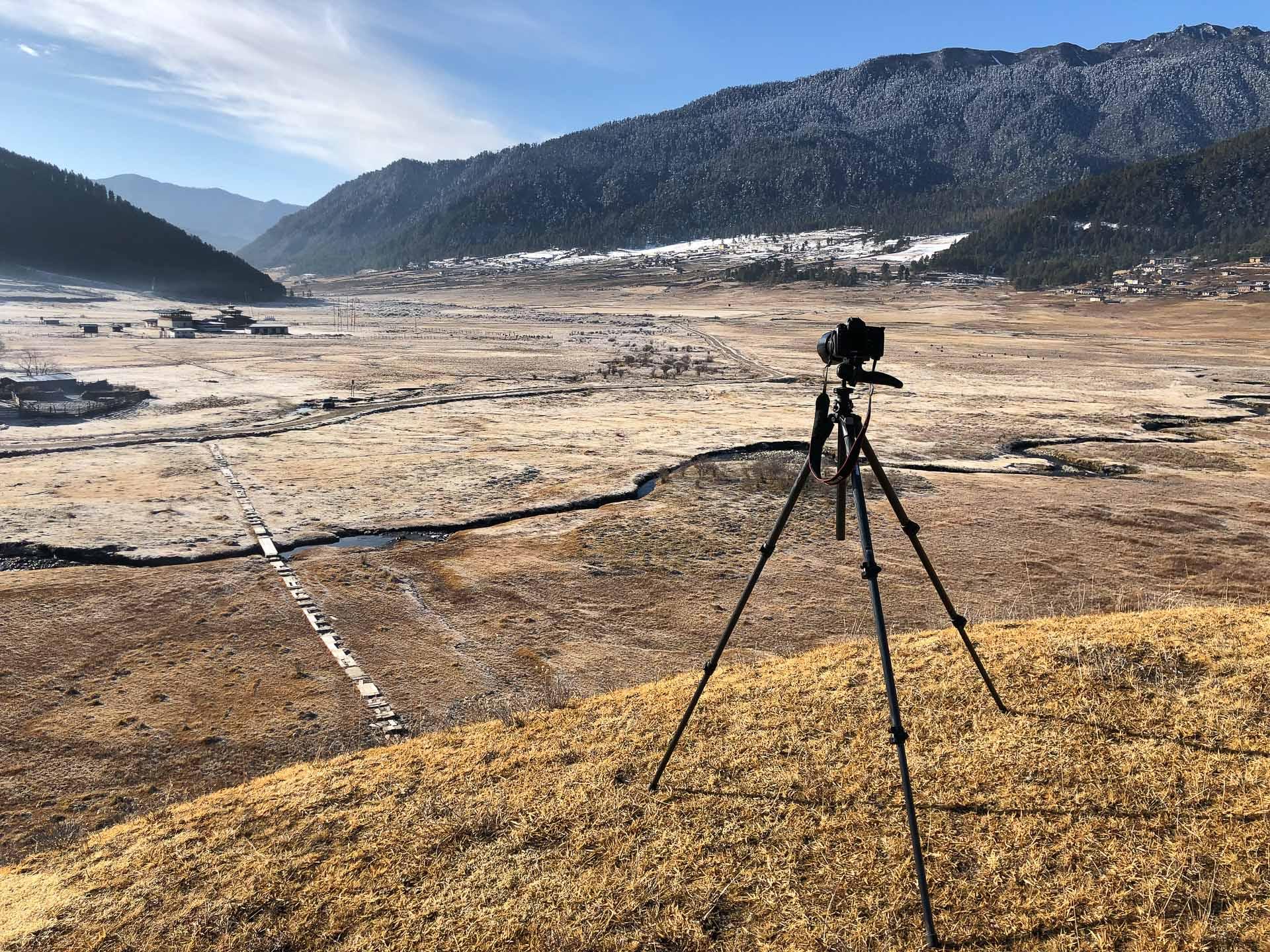 Camera on a tripod overlooking a vast landscape