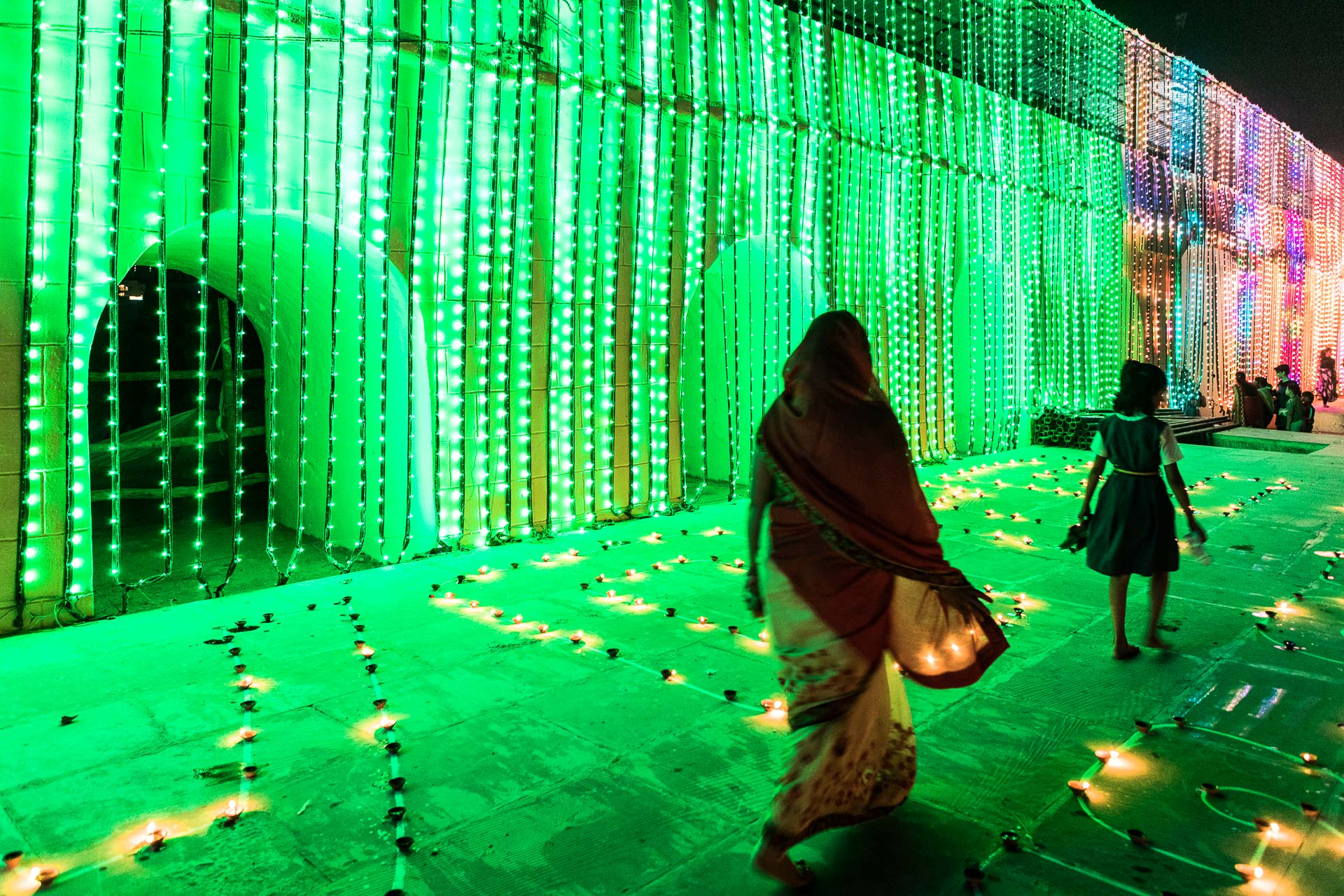 Two people walk past candles on the ground with a heavy green light source in the background
