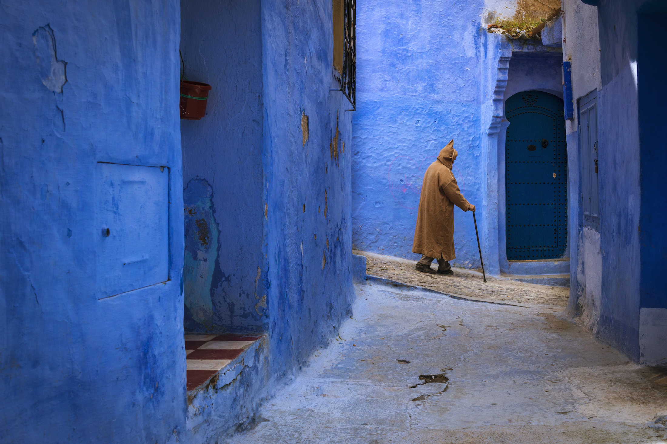 Berber man walking in a narrow street in the town of Chefchaouen in Morocco, North Africa