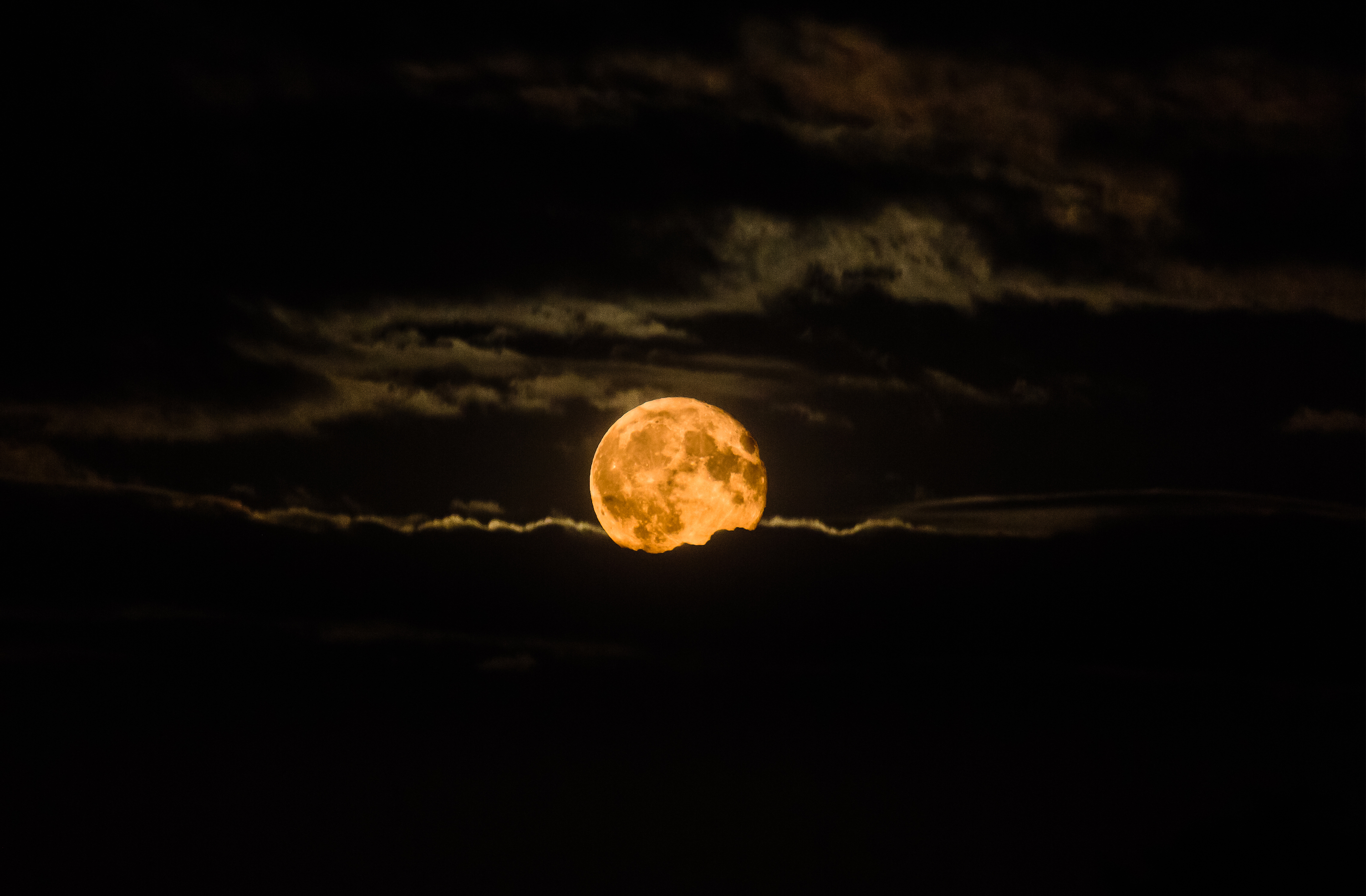 red 'Harvest Moon' rises through a drift of clouds on a September evening