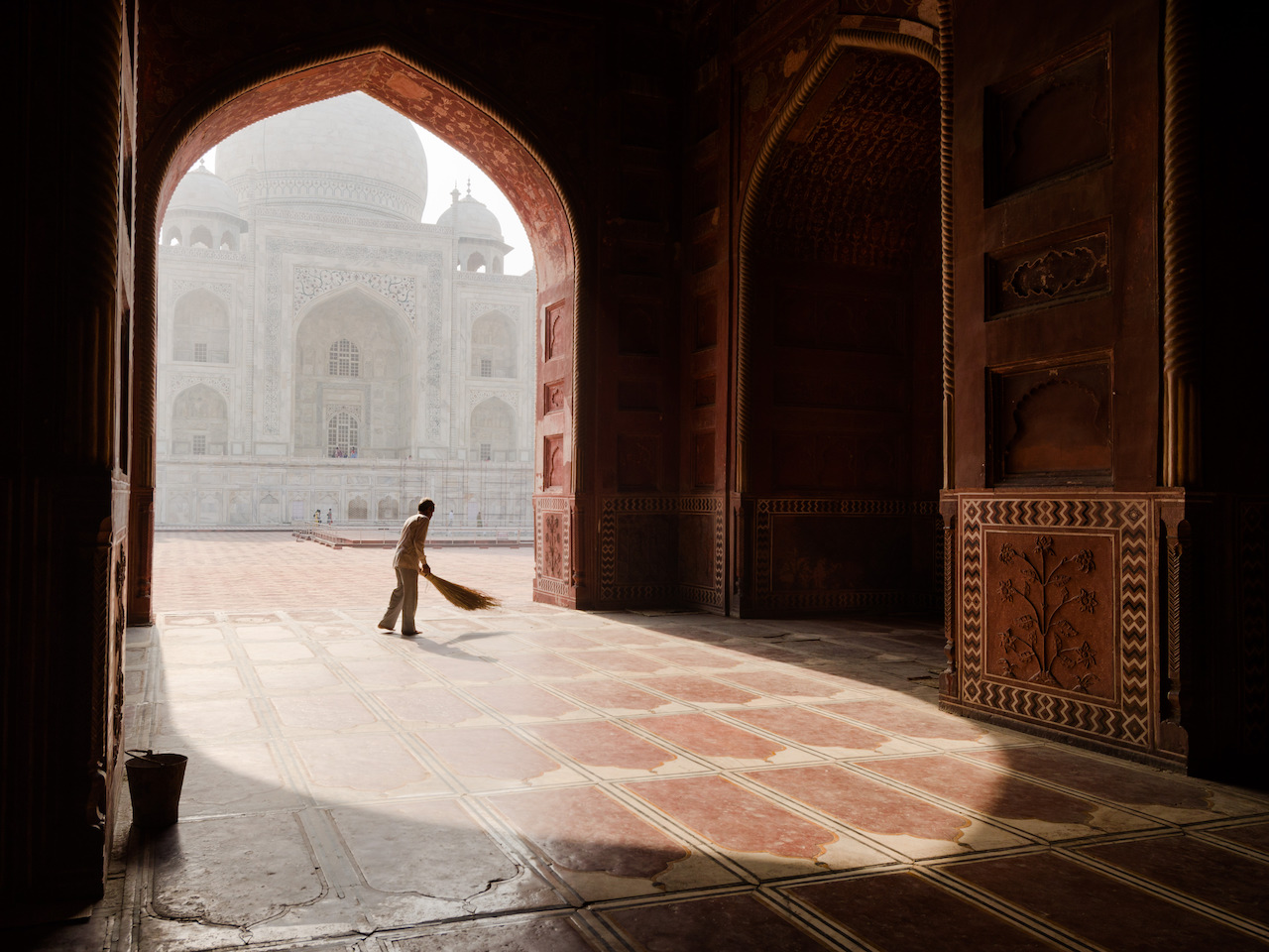 A man sweeps the prayer room in the Taj Mahal main mosque before the Friday prayers
