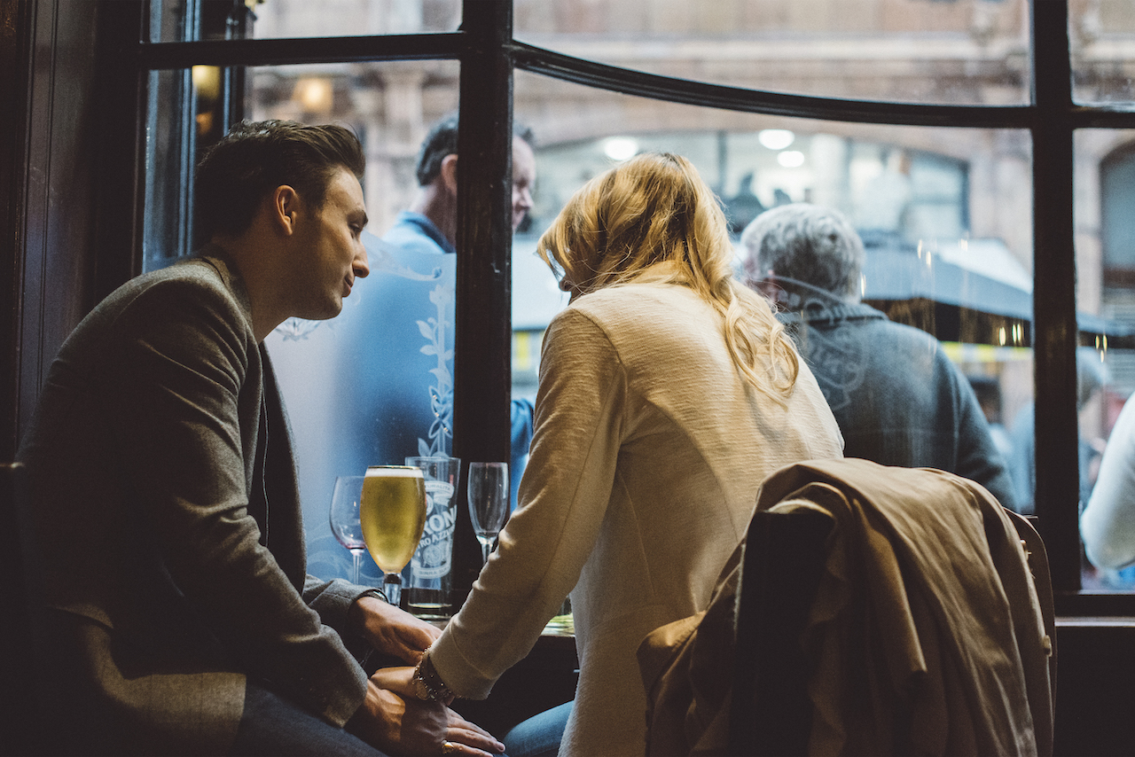 Backlit romantic scene of couple holding hands and talking whils having a drink at a bar in London's West End.