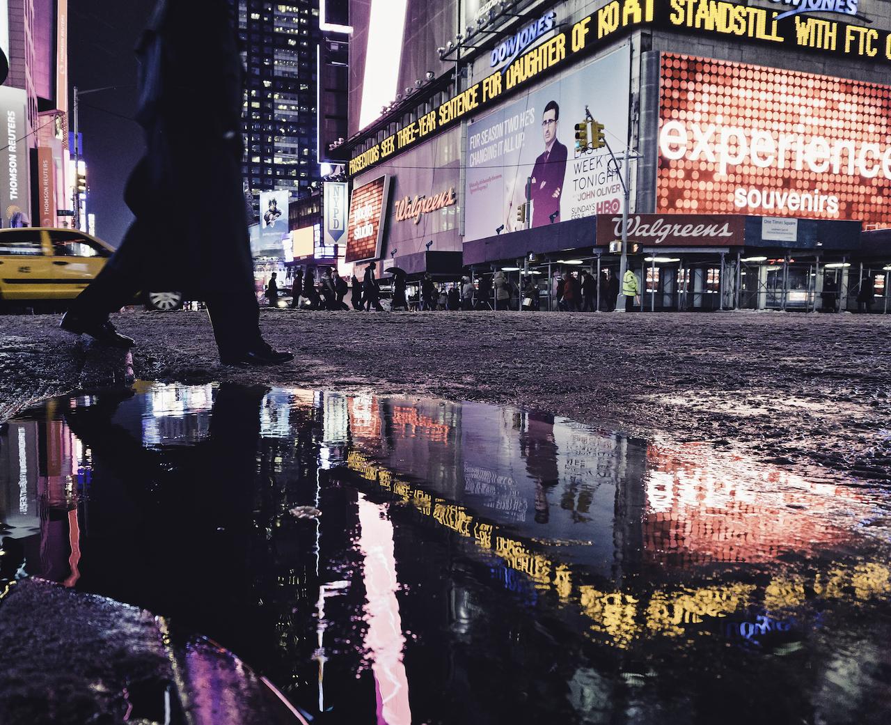 Man crossing the slushy street during the winter in New York City, USA