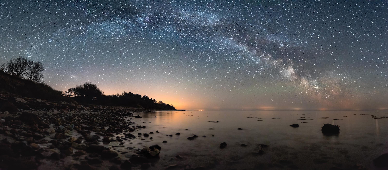 Milky way arc over a beach coastline.