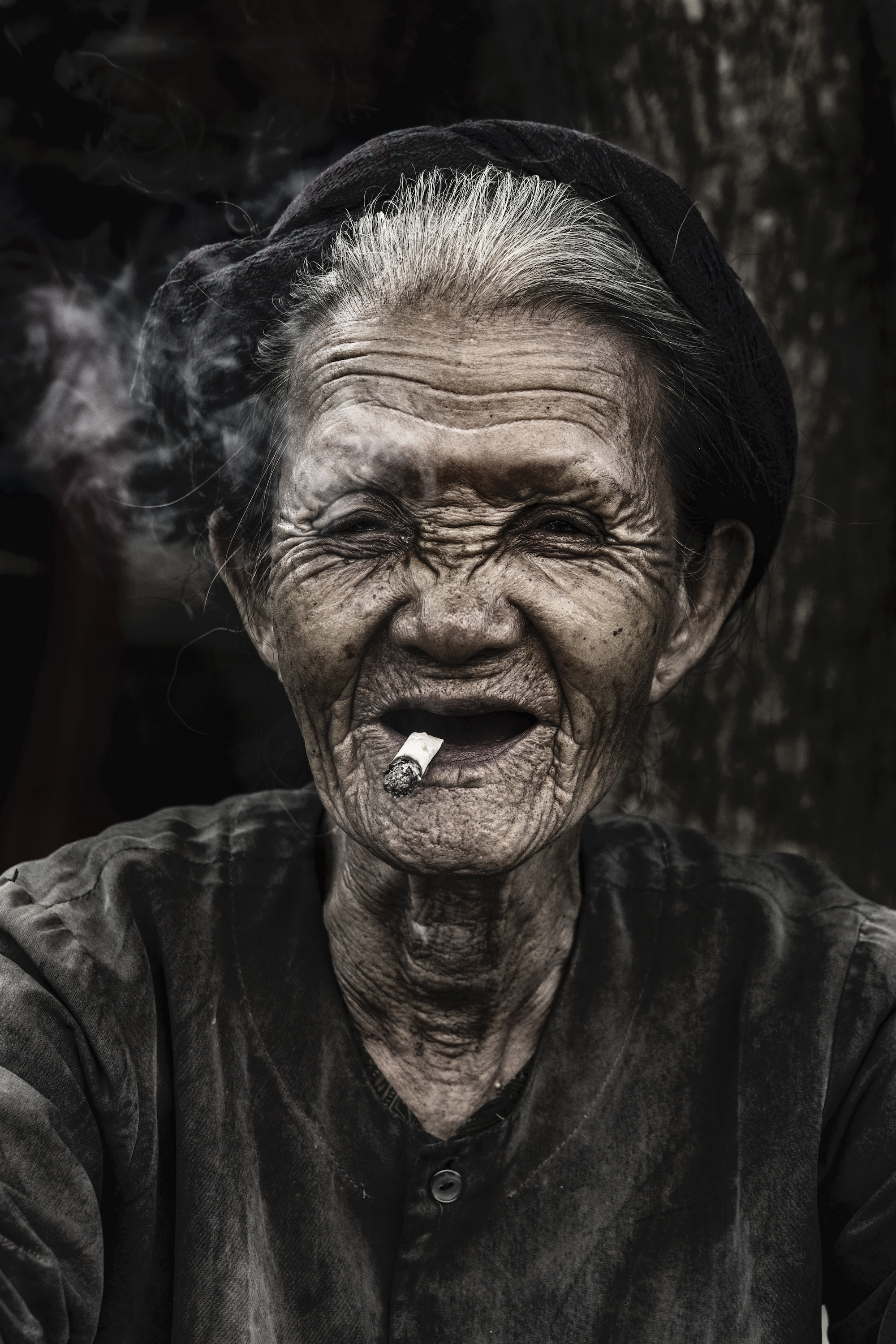 An old woman is smoking a traditional tobacco in a market at Hoian