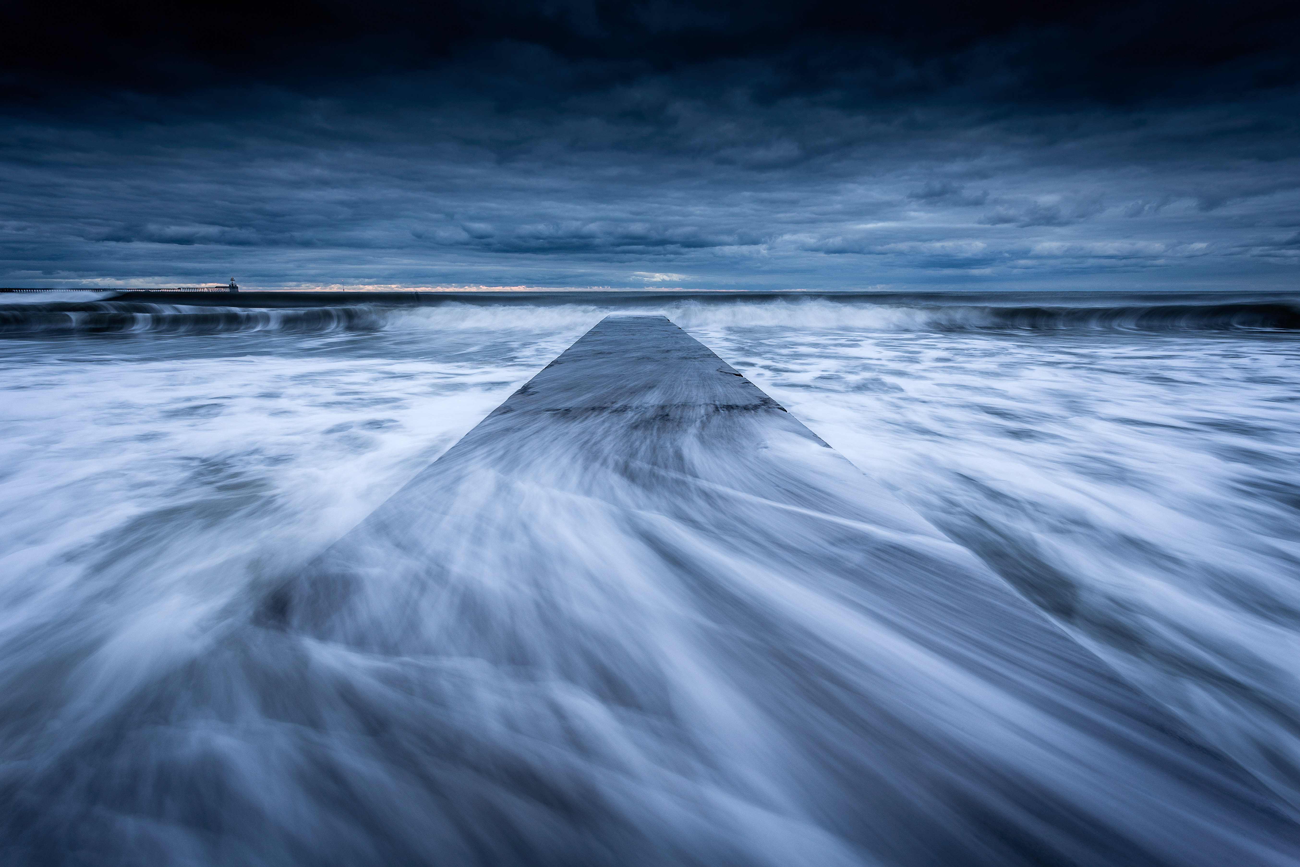 Waves sweep across the concrete jetty at Blyth Beach on the Northumberland coast.