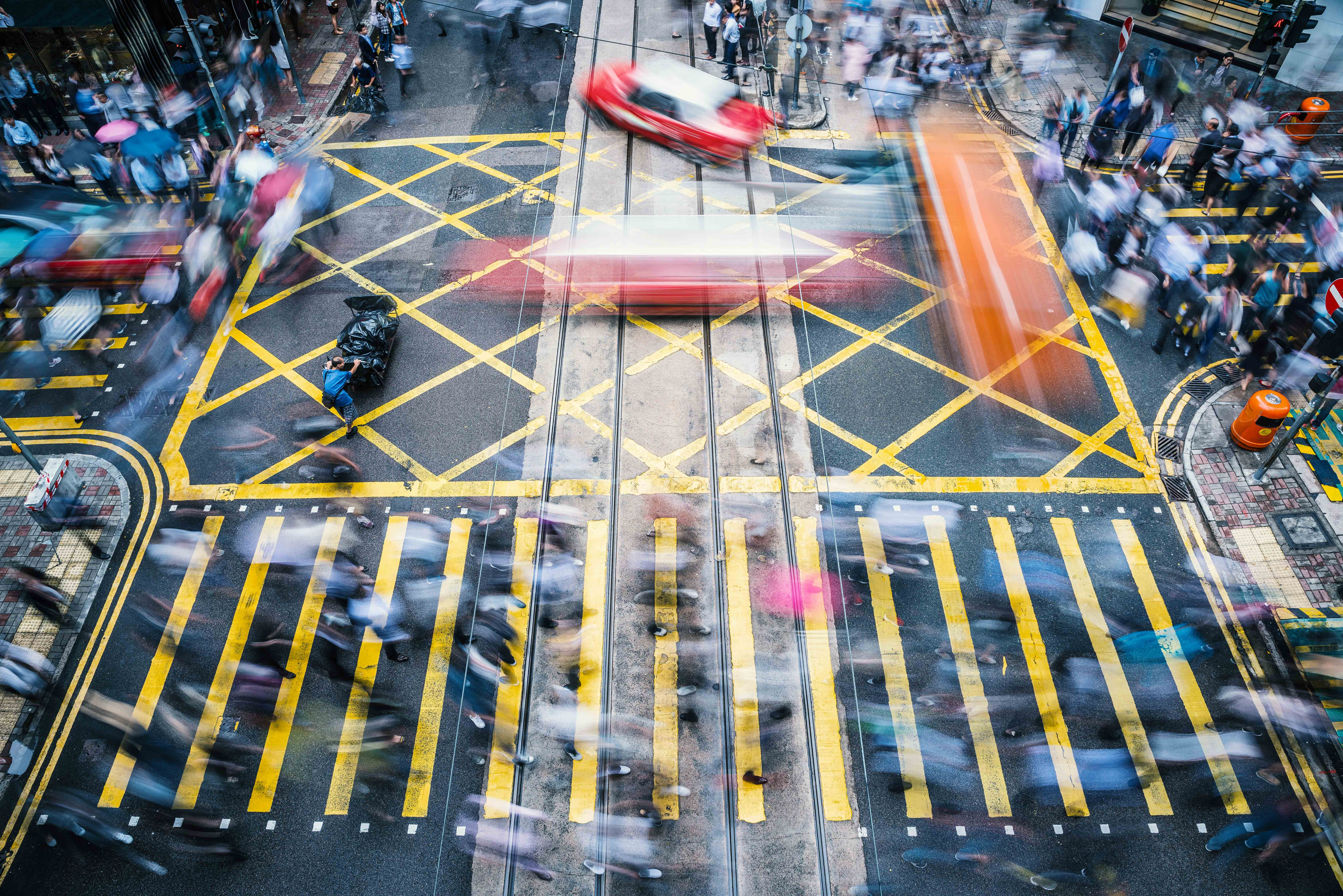 People and taxi cabs crossing a very busy crossroads in the central district, Hong Kong