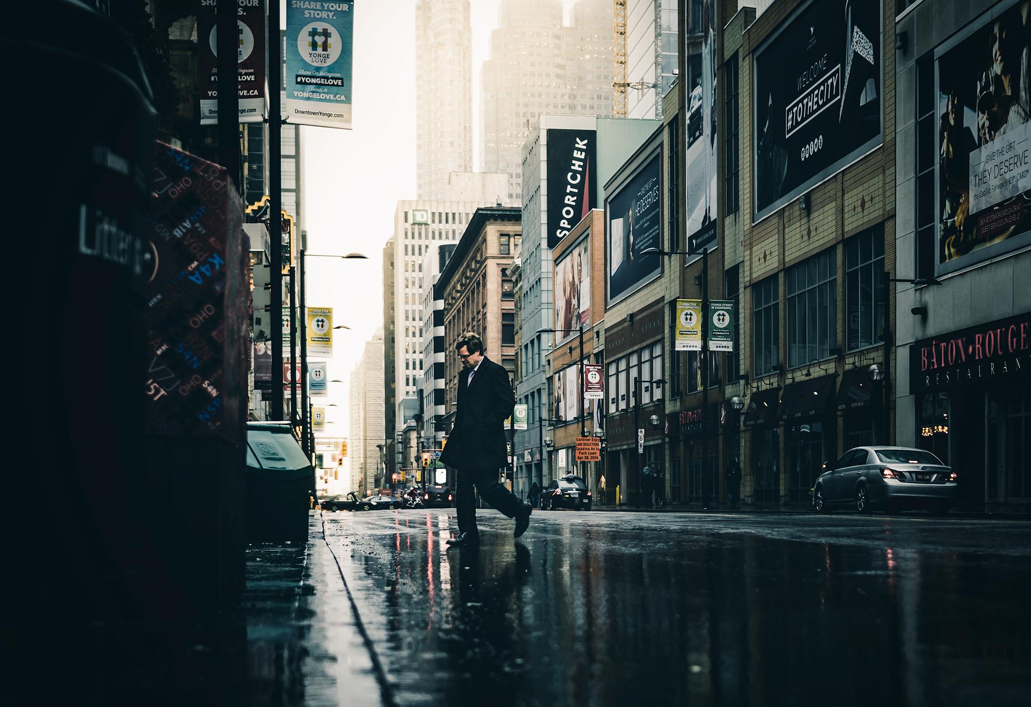 Man crossing the street during the rain. Toronto, ON, Canada.