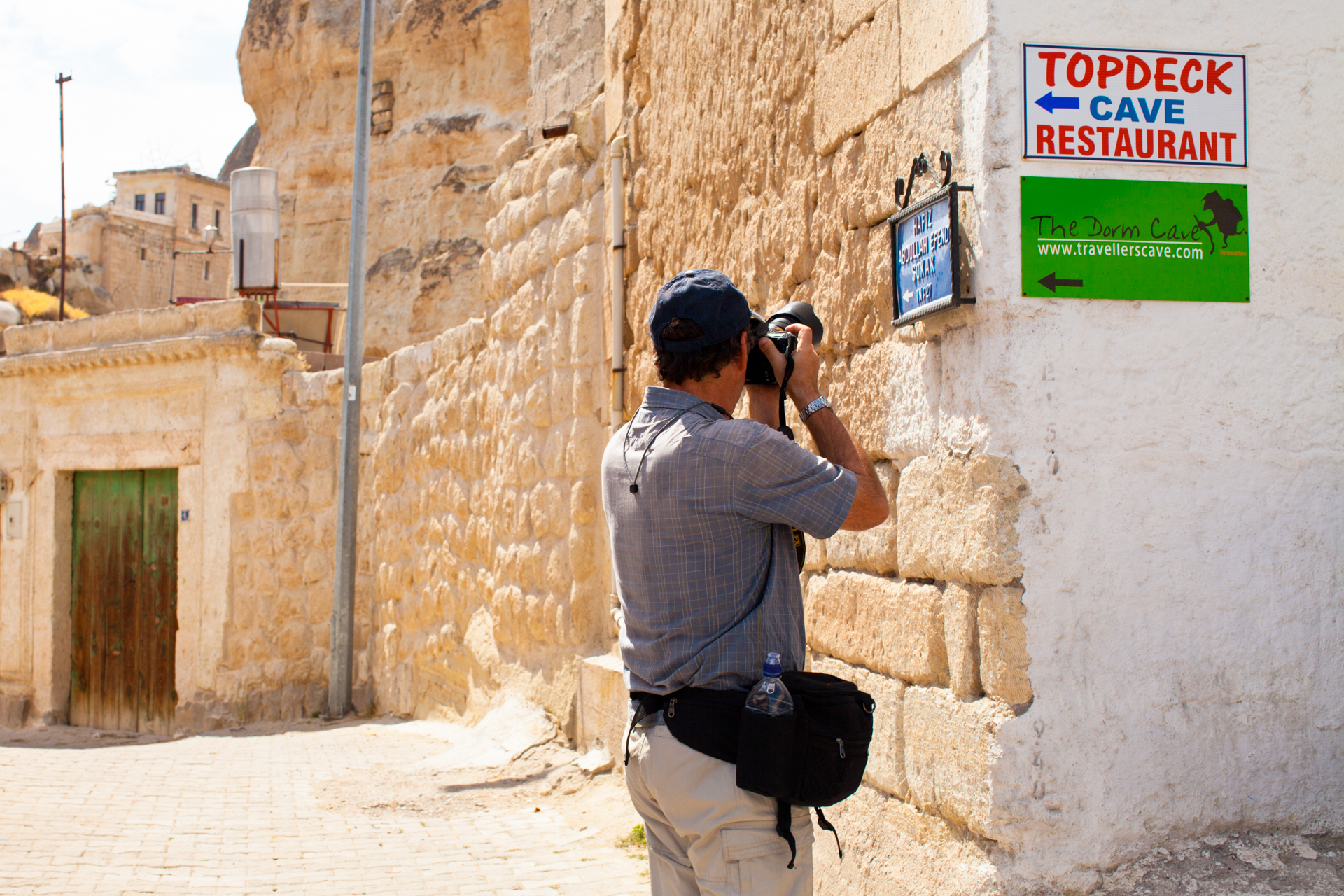 Man photographing a street sign