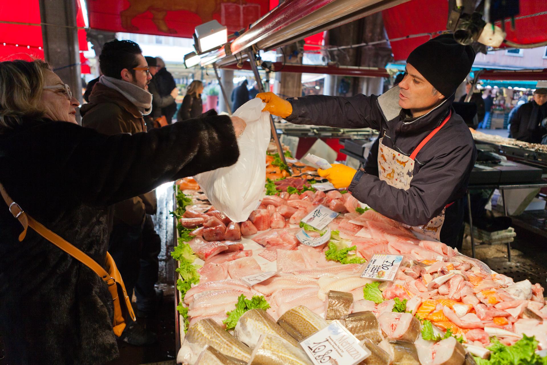 Customer and vendor at the Rialto market in Venice.