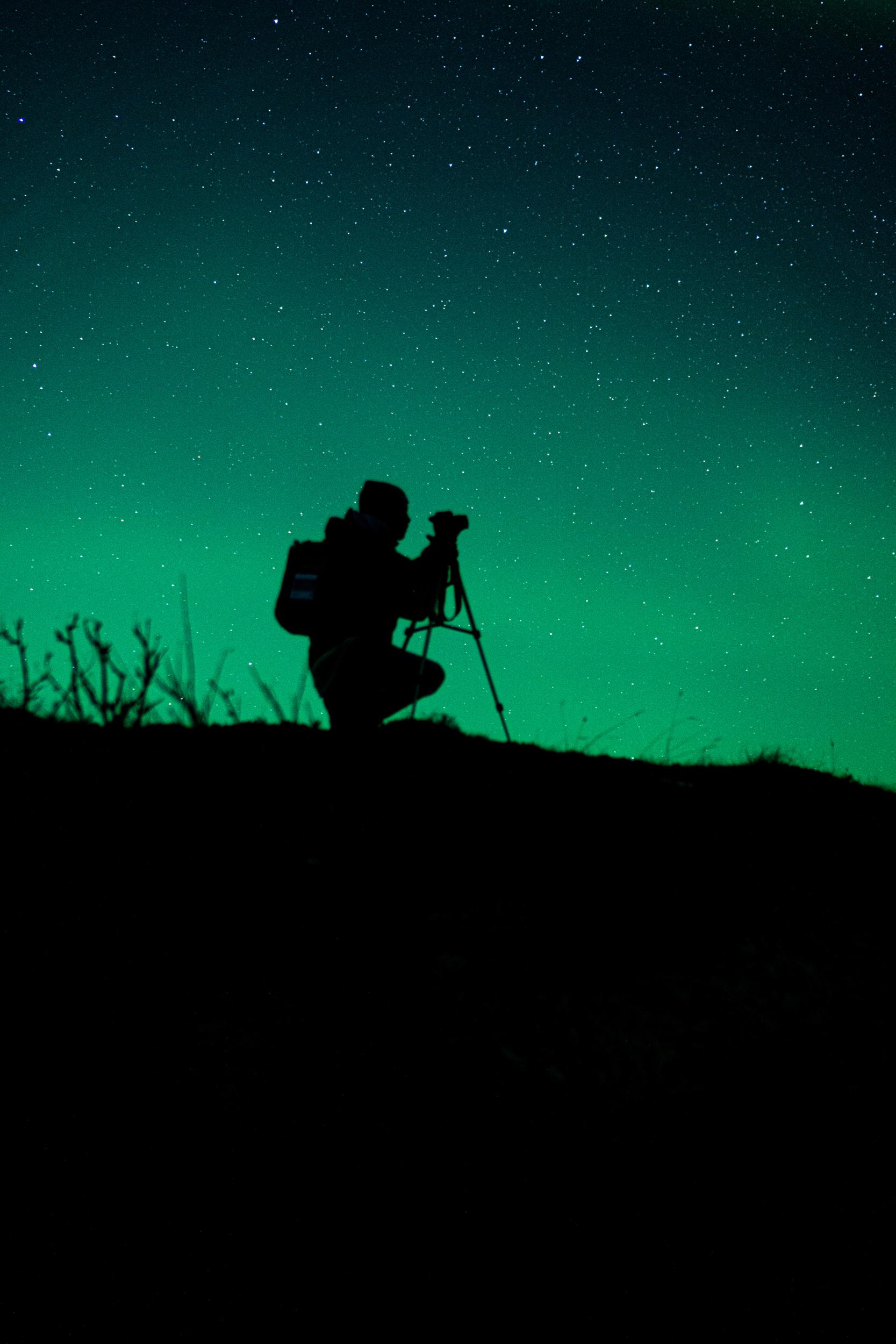 A photograhpher setting up to photograph the Aurora Borealis