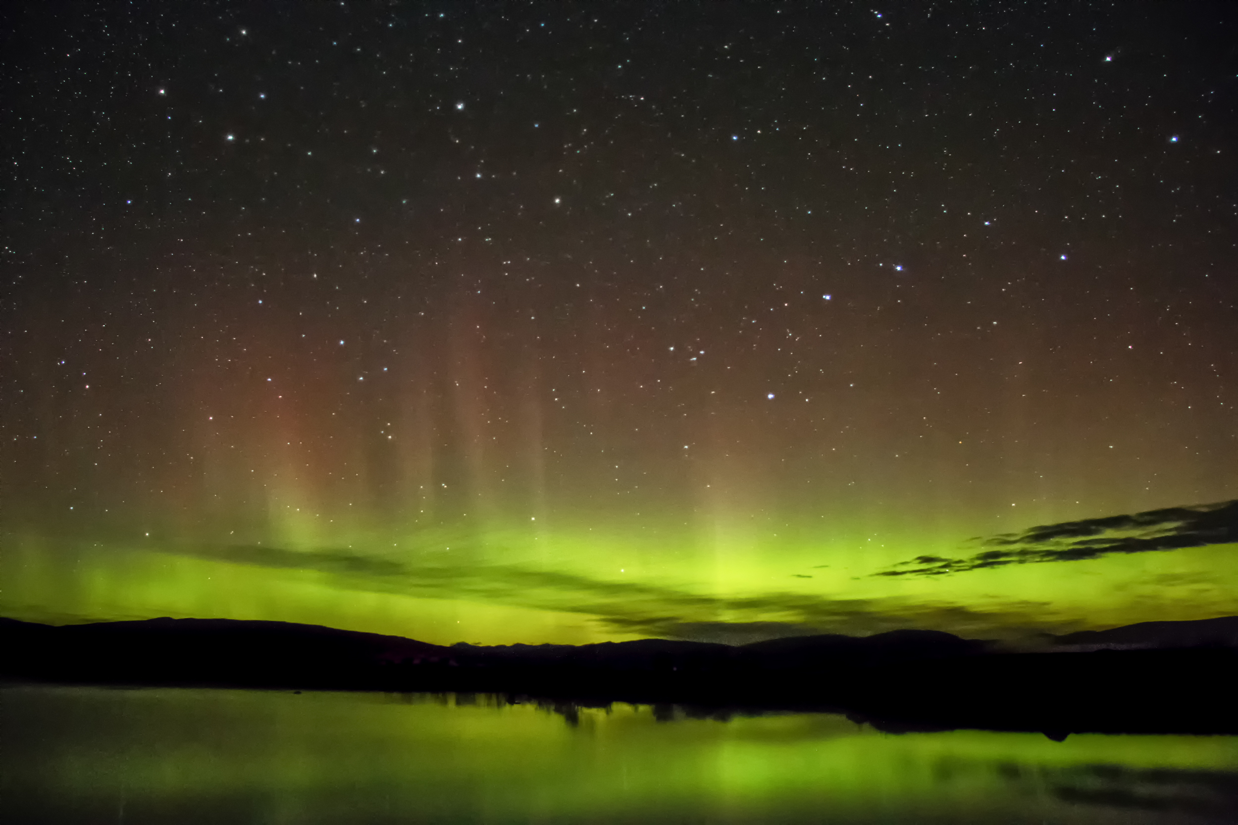 A faint aurora over a loch in Scotland