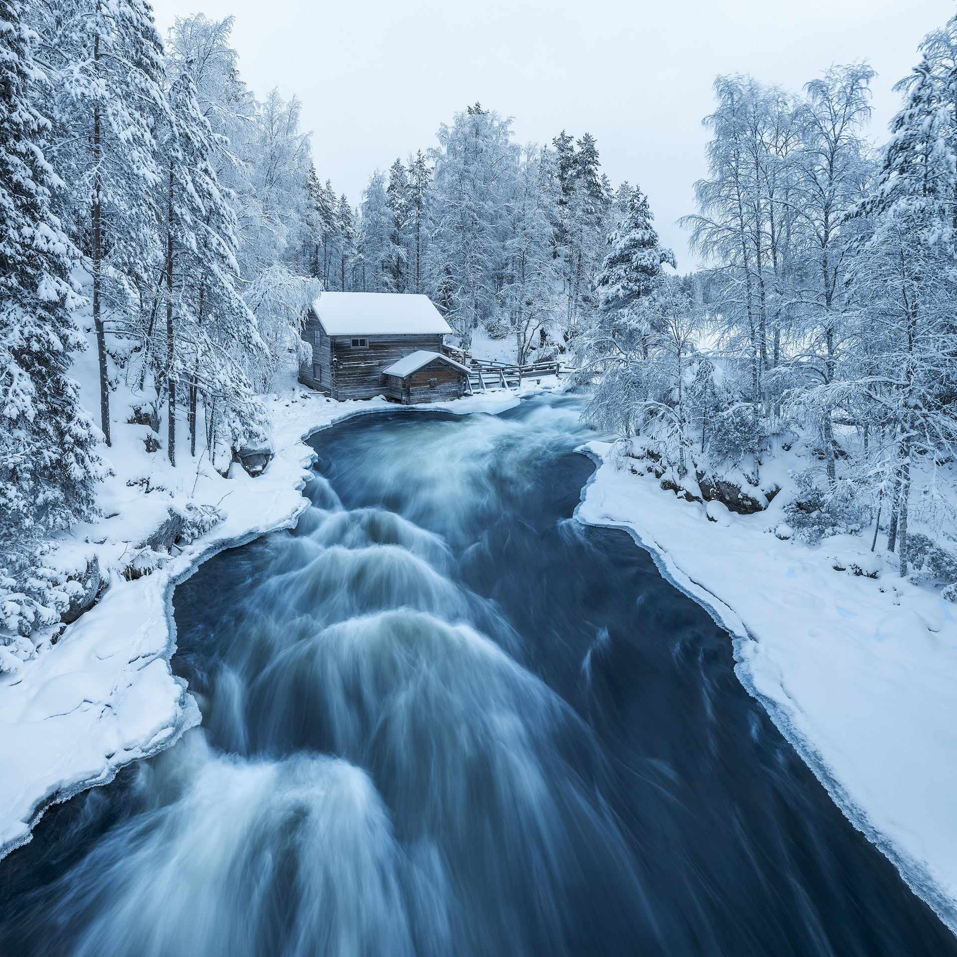 Wooden house and flowing river in wintry conditions