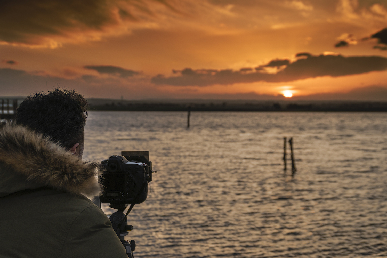 A photographer takes pictures at sunset with an ND filter
