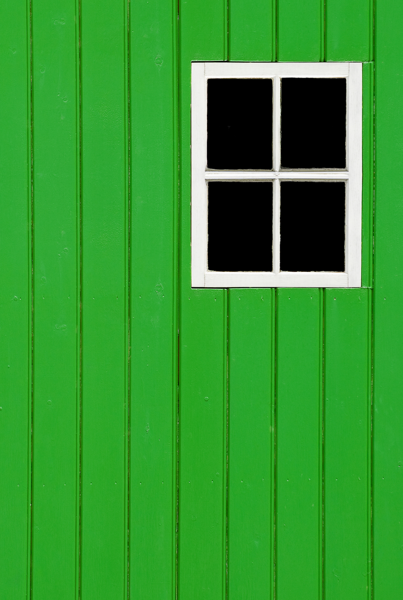 Building side view of a green wood panel frame with blank windows