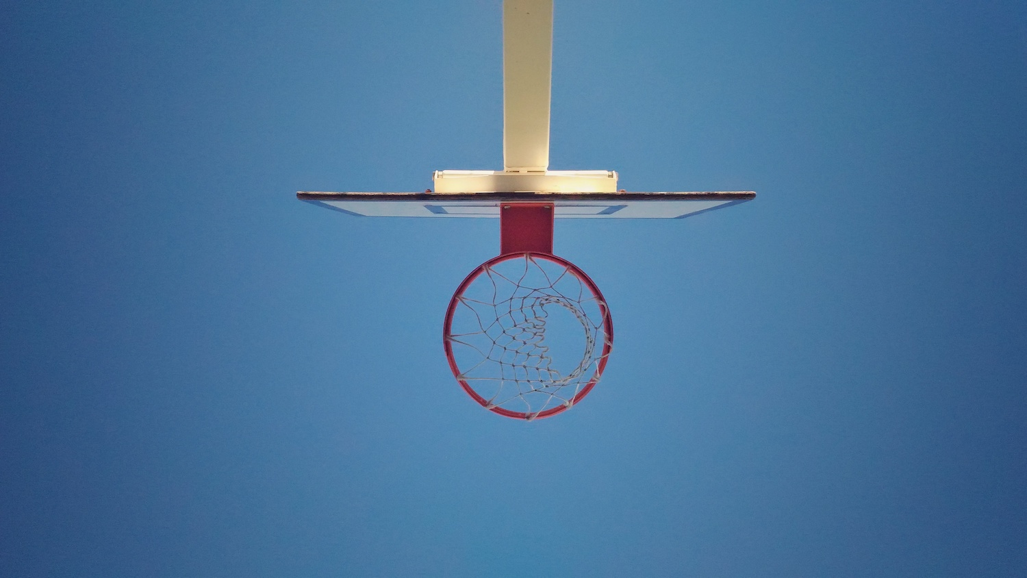 Basketball basket viewed from bottom to top against a blue sky