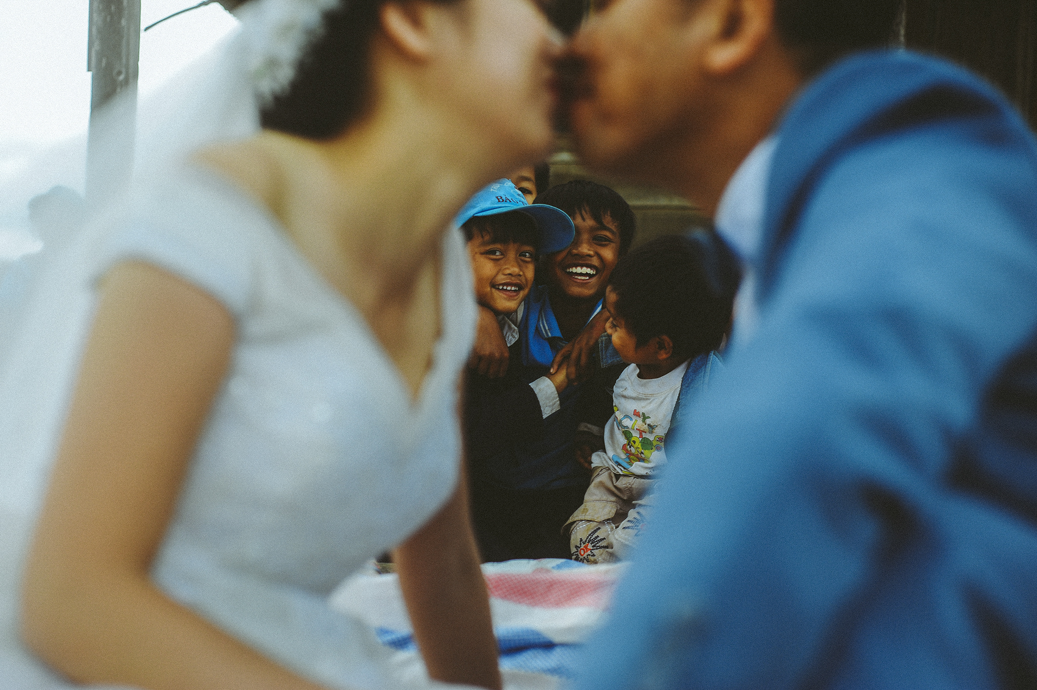 Bride and groom kissing with kids in the background