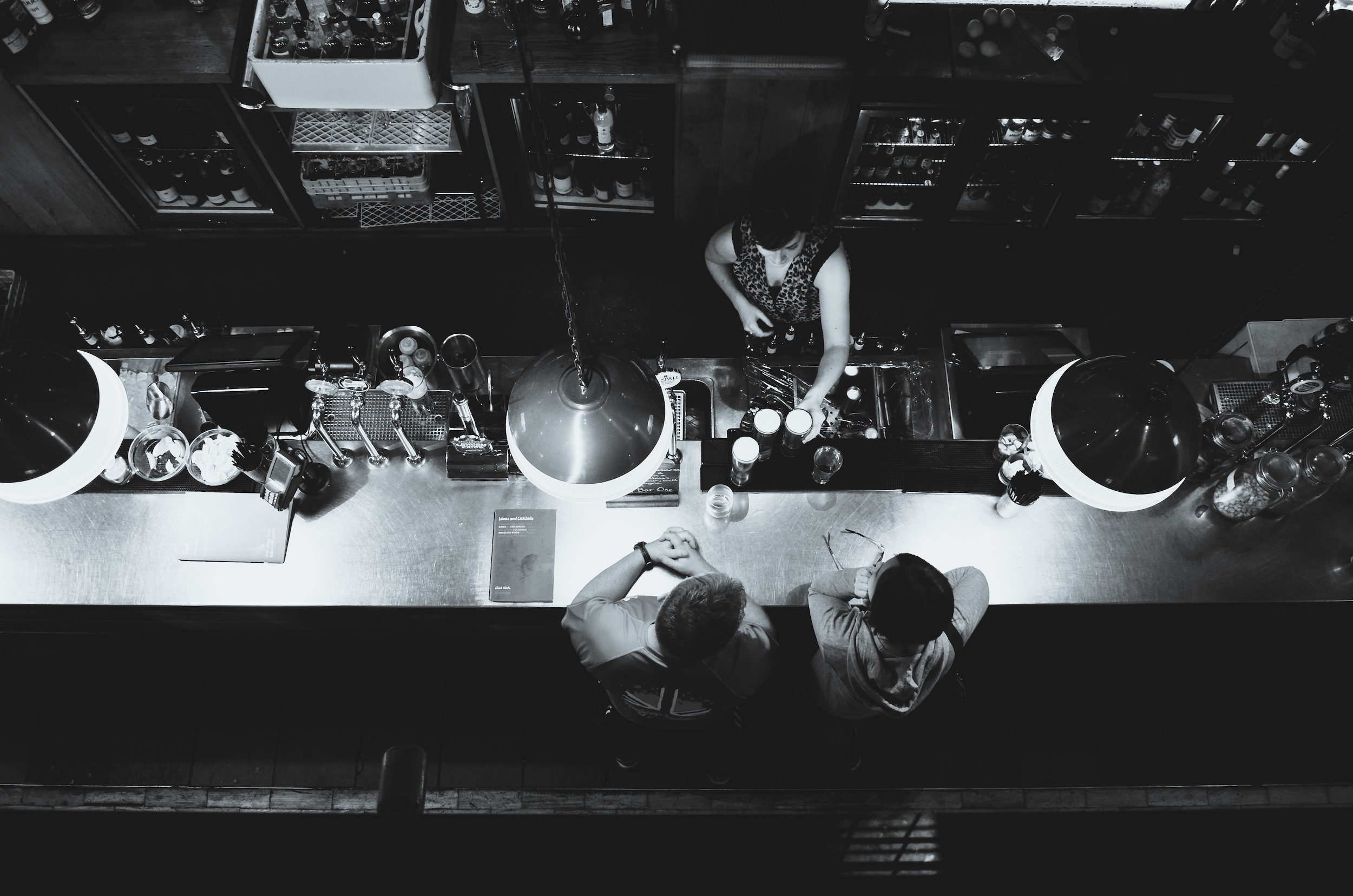 Overhead view of two people drinking in a bar