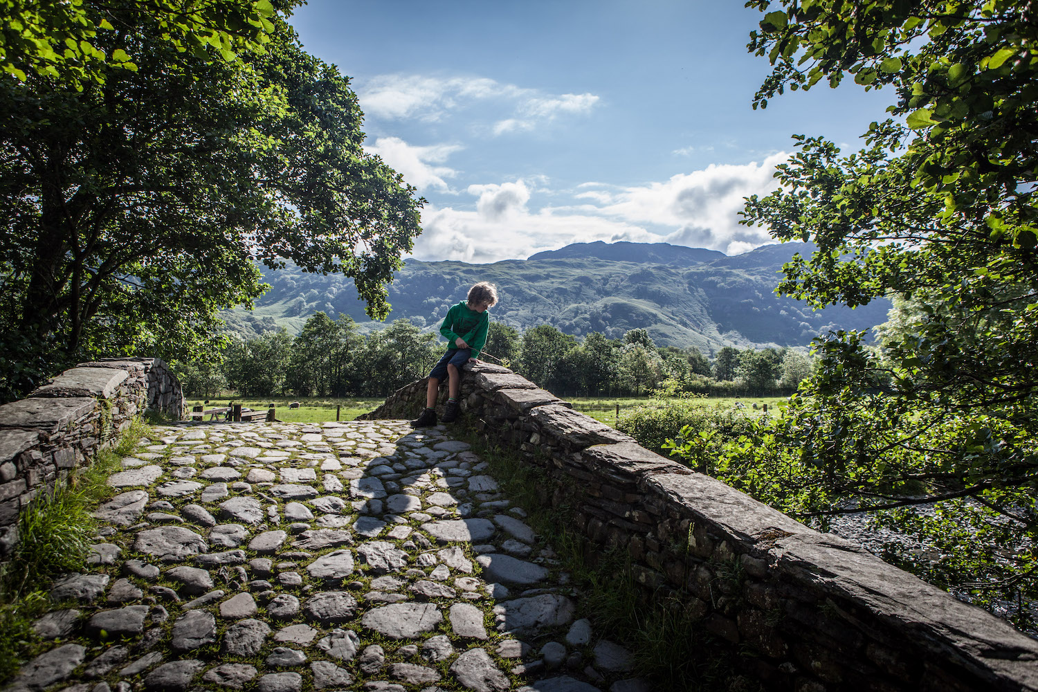 Boy looking over a bridge in the Lake District, England