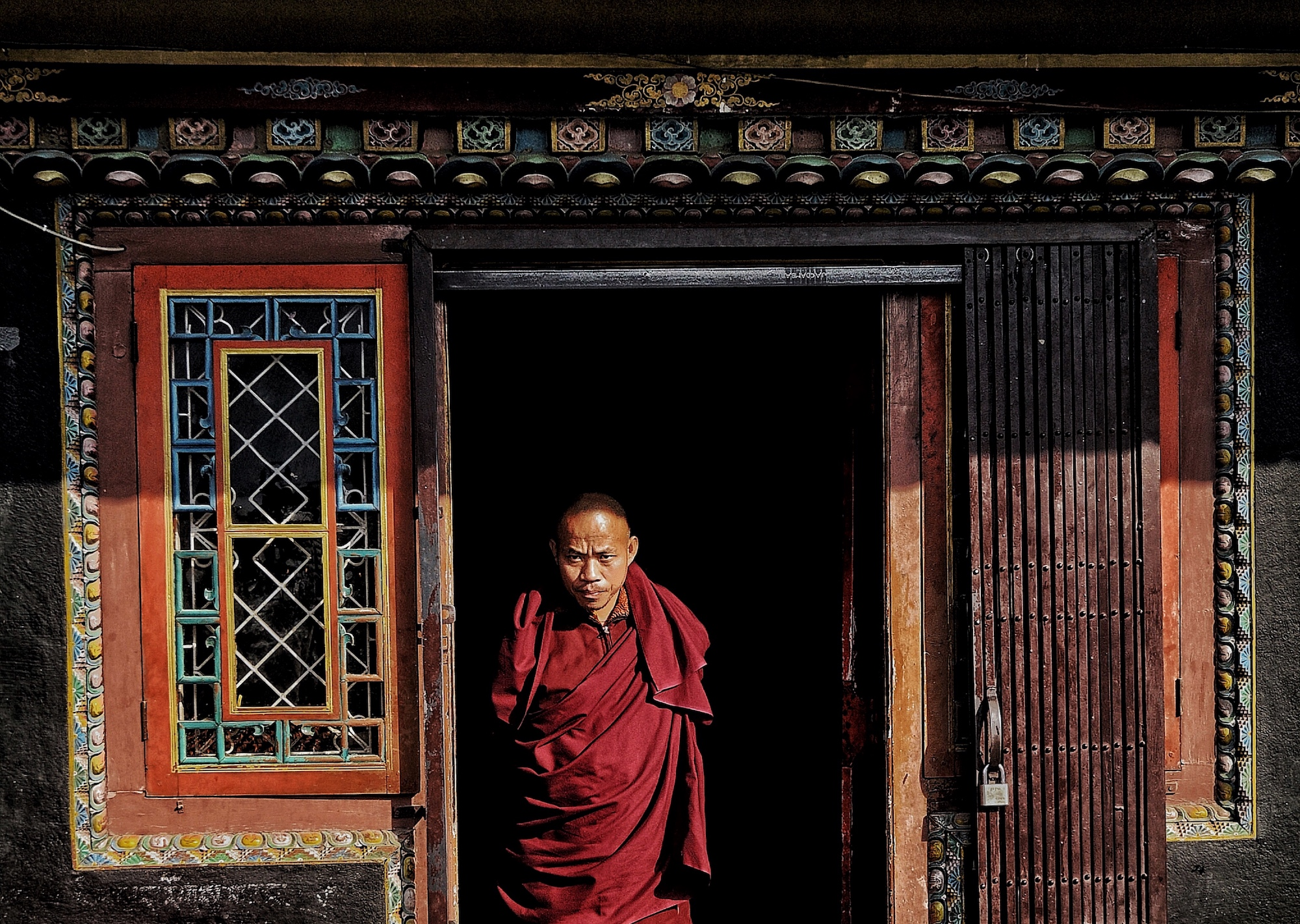 Buddhist monk standing in front of the colourful door