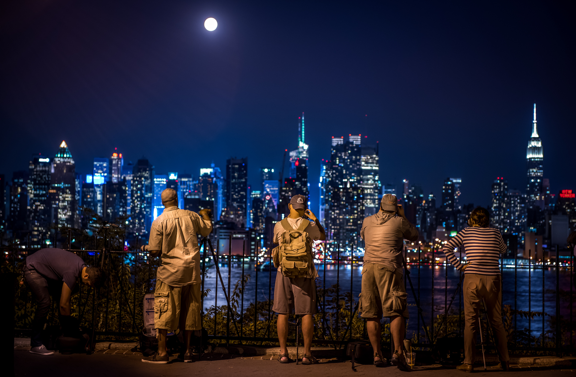 Photographers taking pictures of the New York City skyline at night