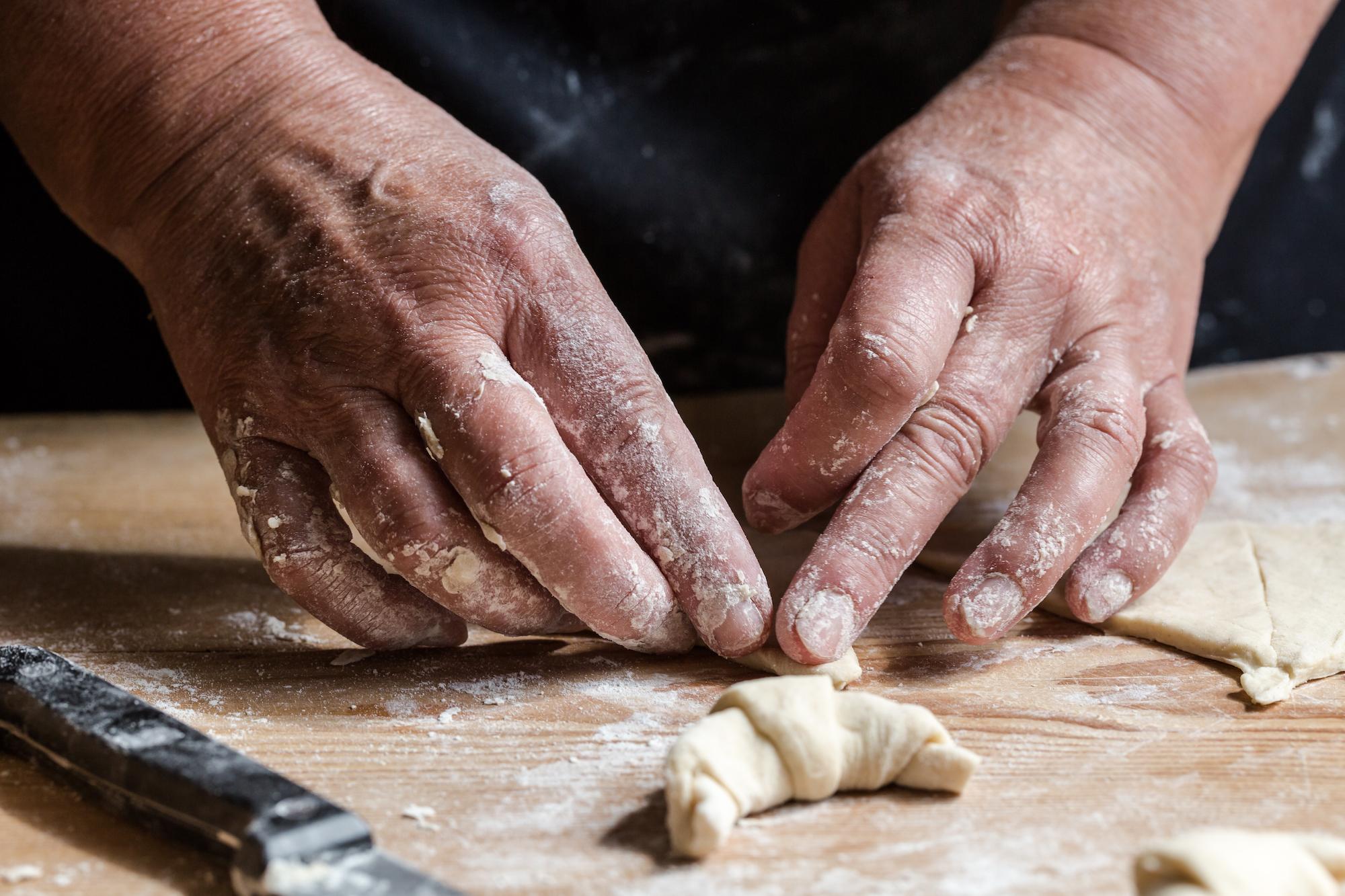Hands rolling fresh homemade croissants
