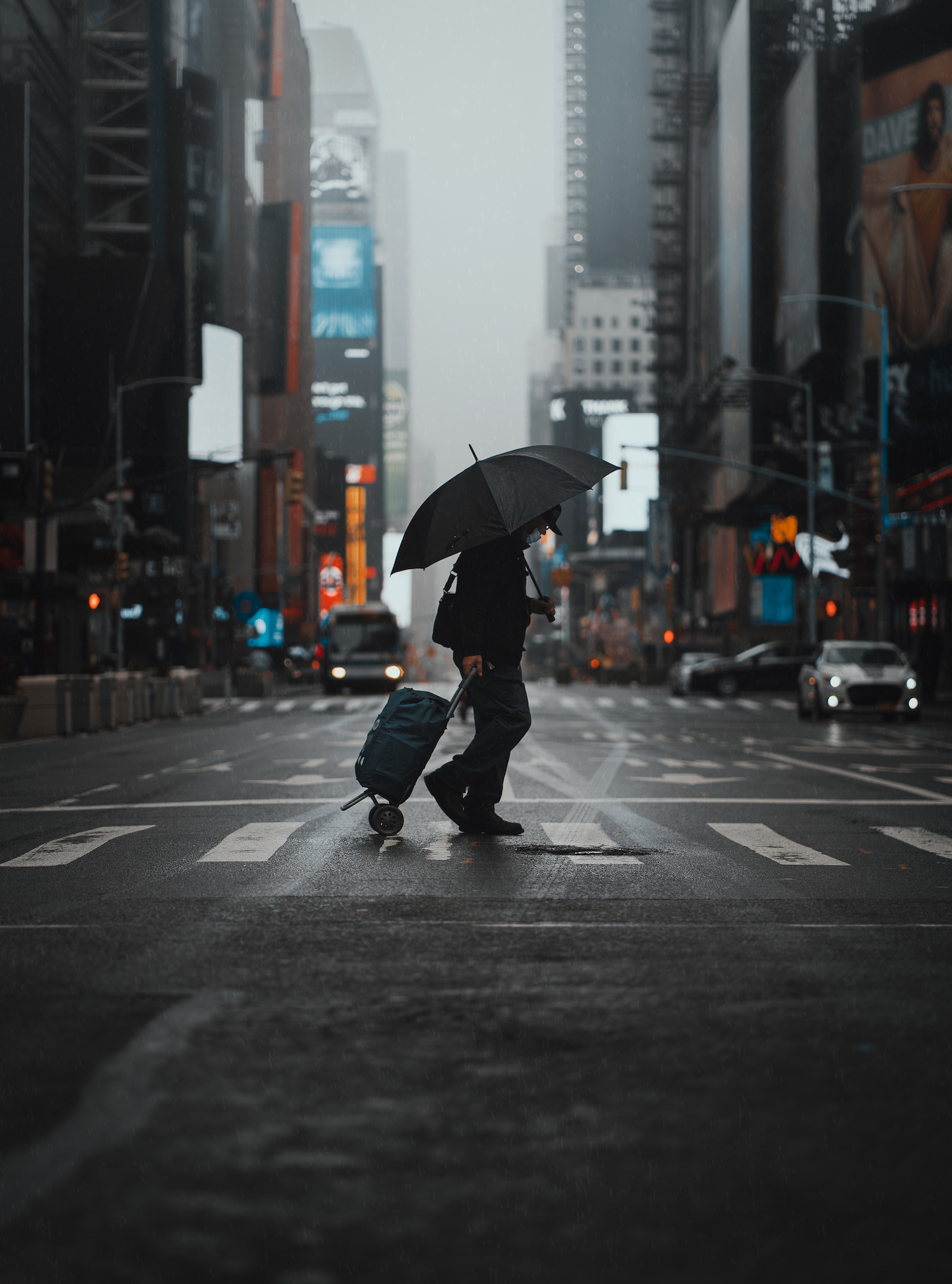 Person with umbrella walking across the street during lockdown in New York