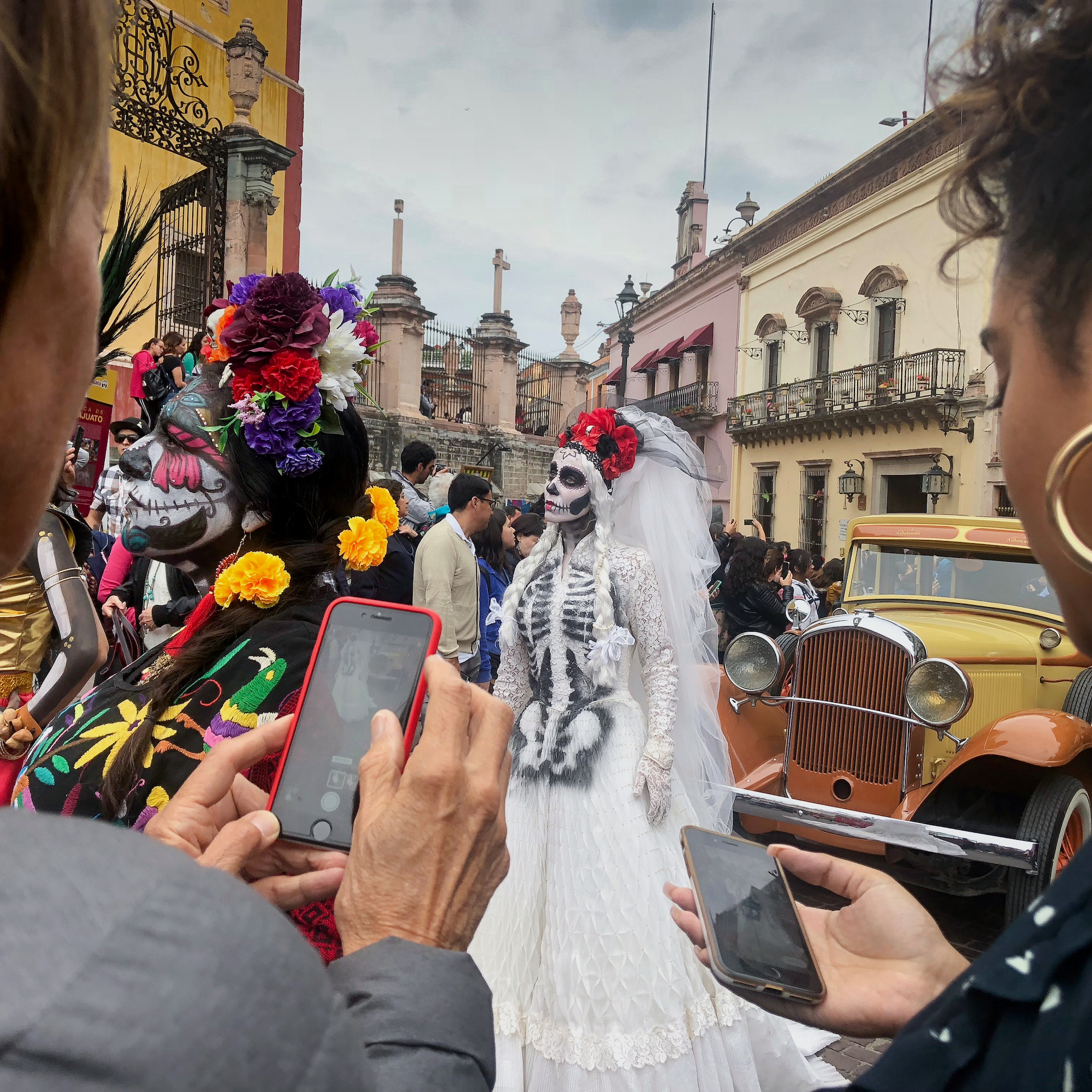 Taking a photo on a smartphone of Day of the Dead celebrations