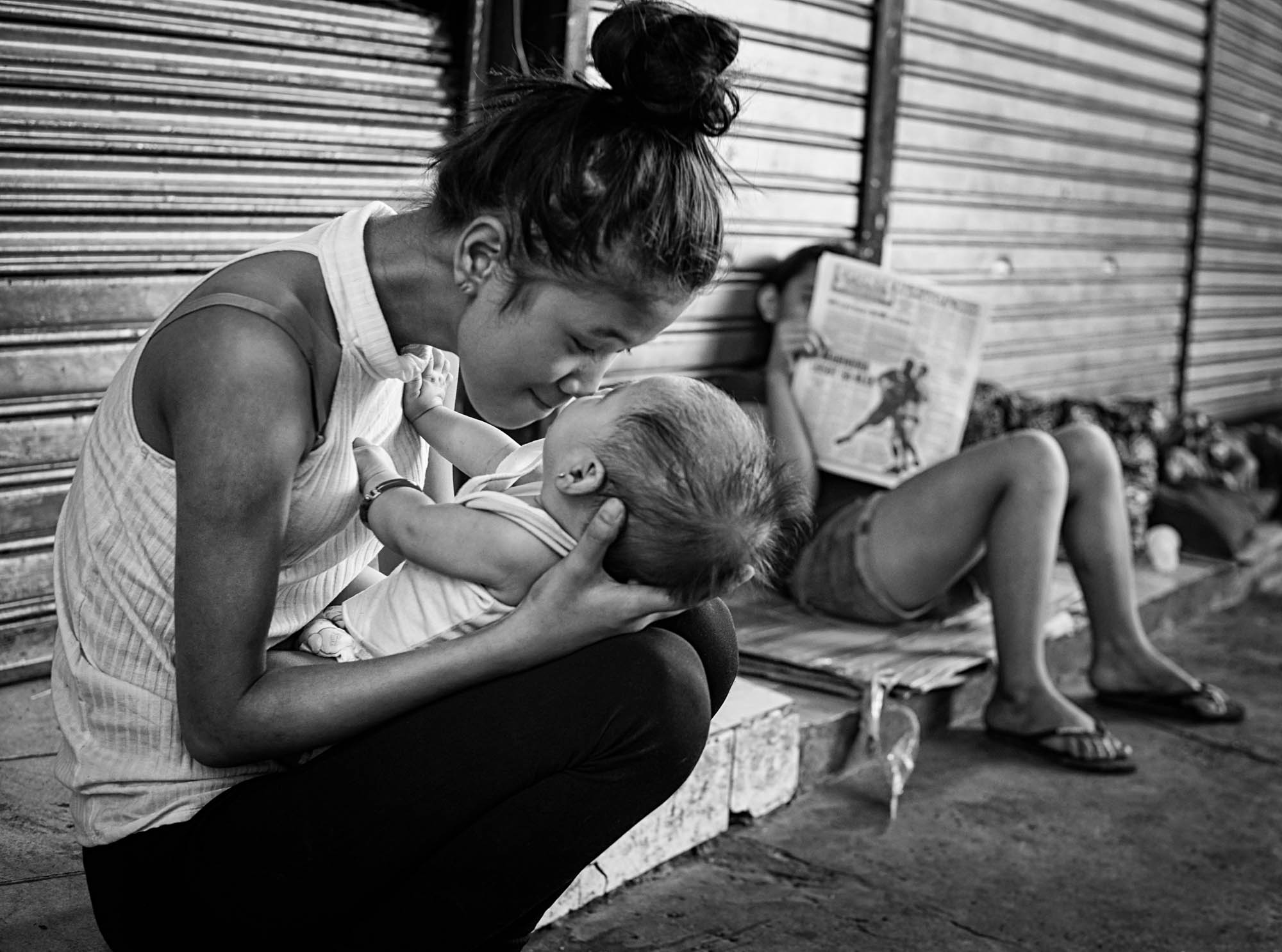 A young mother plays with her child on the street of Manila, Philippines