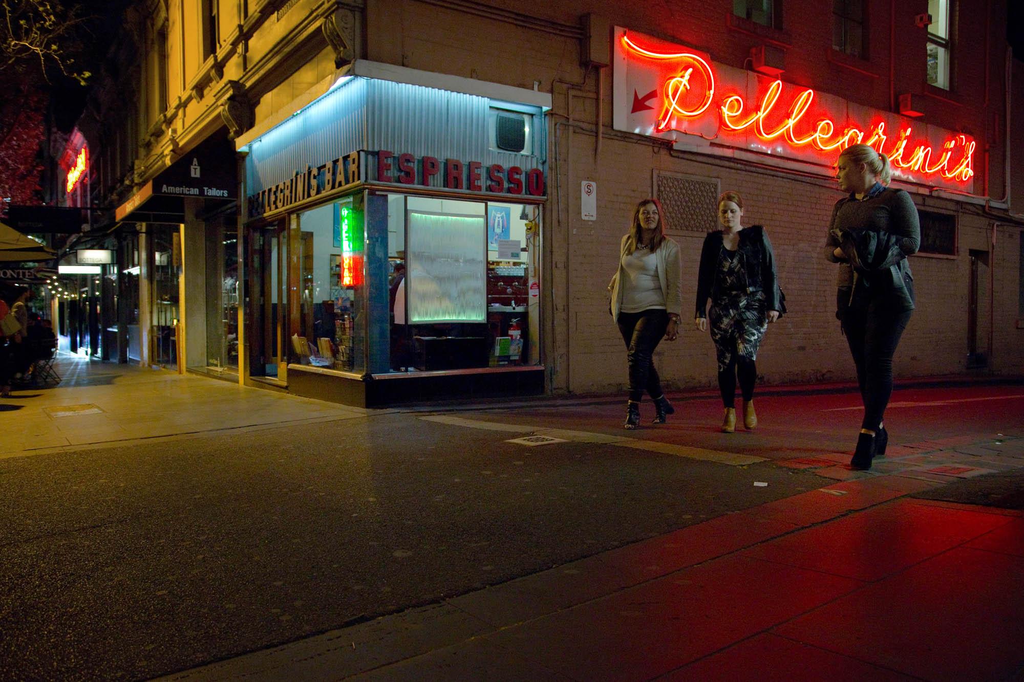 Three people walk past Pellegrini's Espresso Bar, Melbourne, Australia