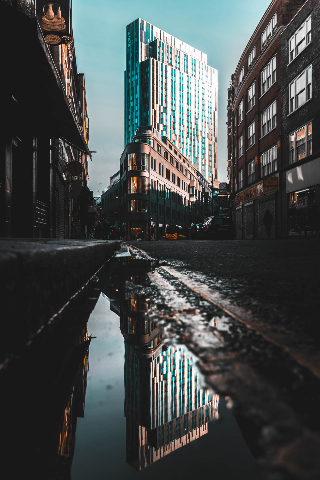 On a bright day in London, a building is reflected in the puddles that remain from the storm the night before.