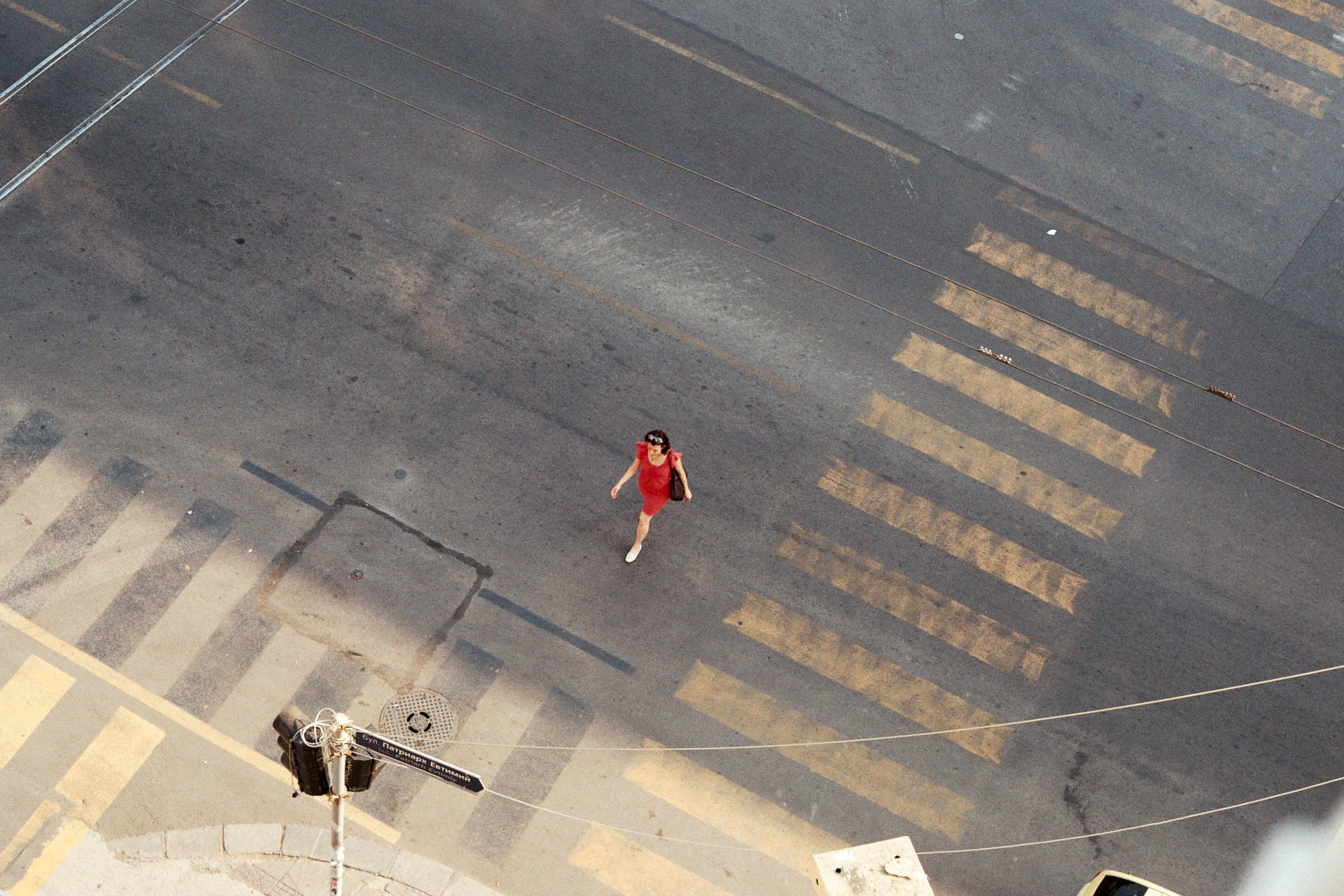 A lady crossing the street in a red dress