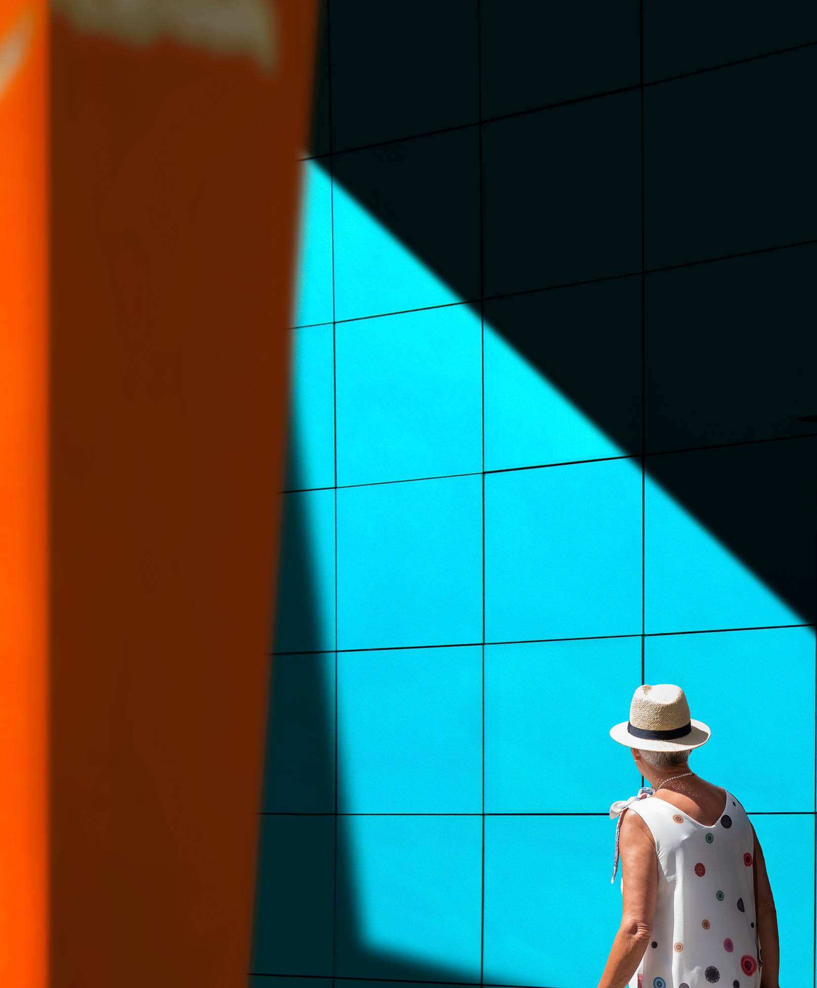 Woman walking down the street against a palette of bright colours and contrasts