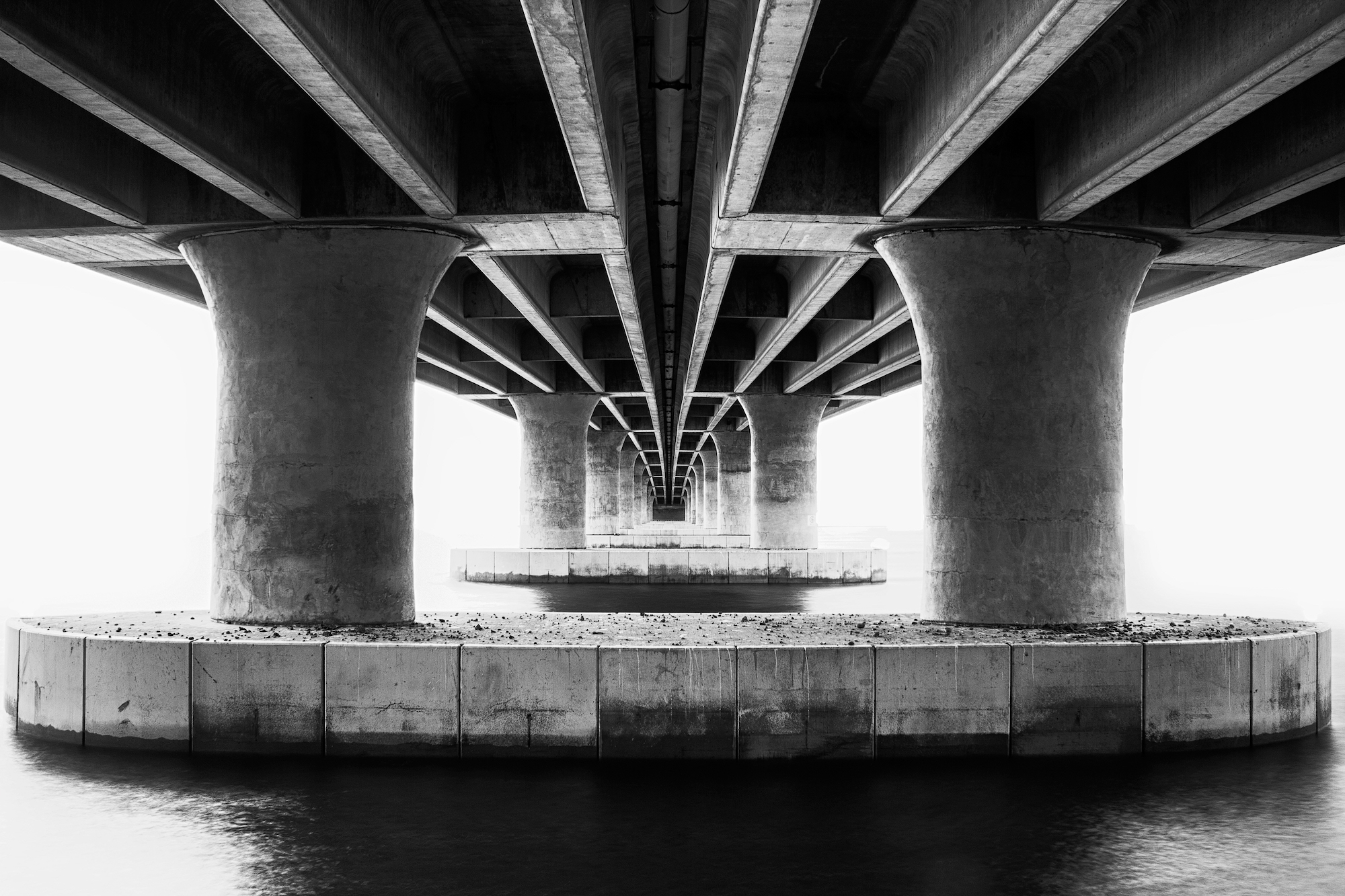 Concrete convergence photographed from underneath a bridge