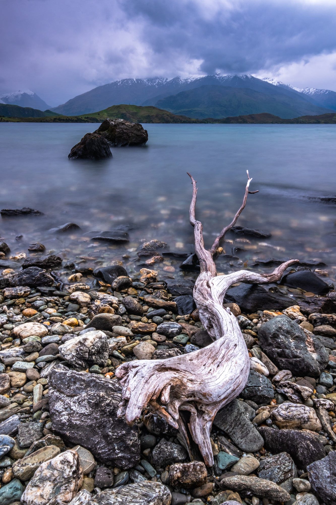 Washed up driftwood and pebbles make for a textured foreground as The Remakables are almost swallowed by low clouds; Queenstown, New Zealand