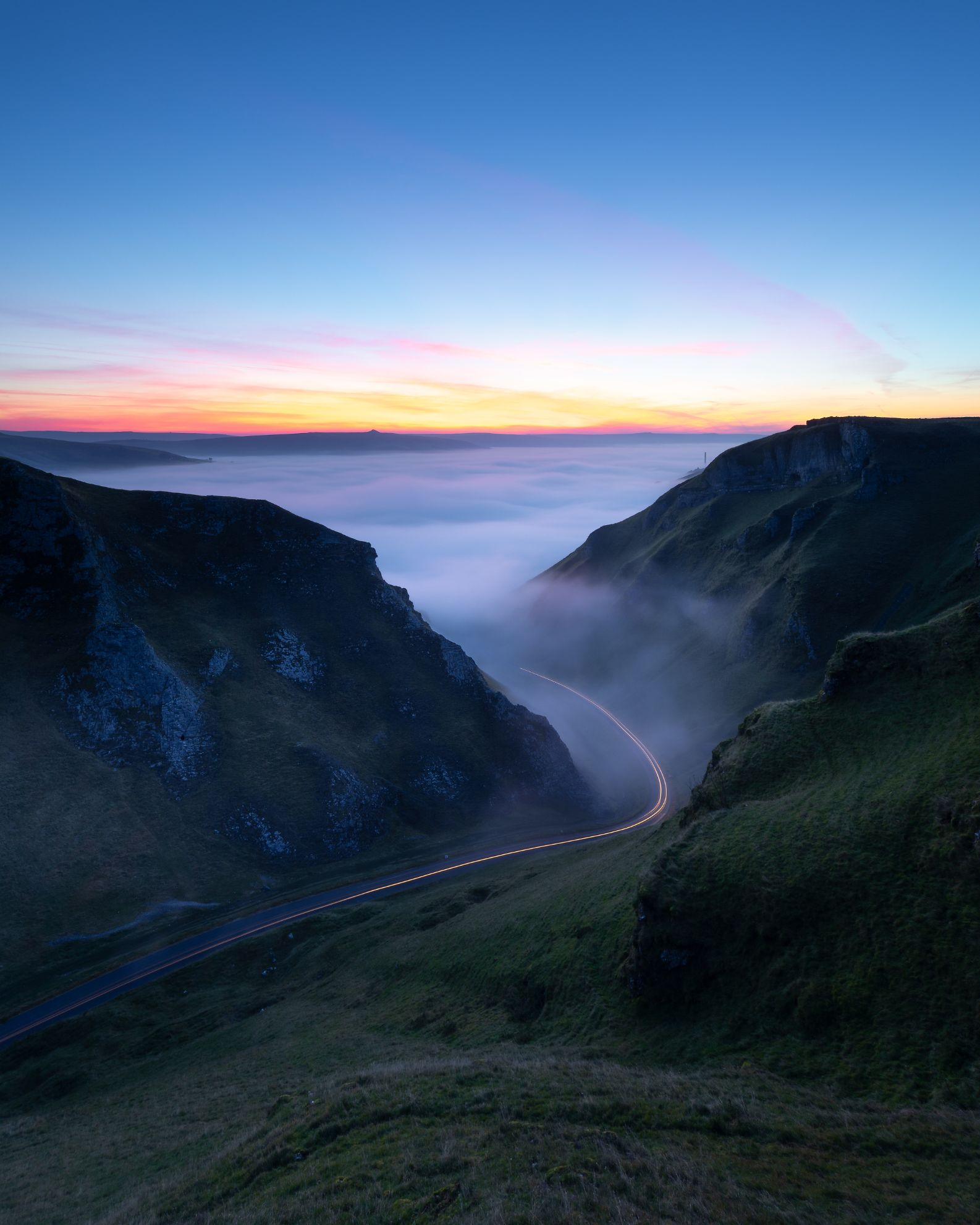 A colourful sunrise at Winnats Pass with a cloud inversion developing early on. A long exposure helped to capture the light trails of an emerging car