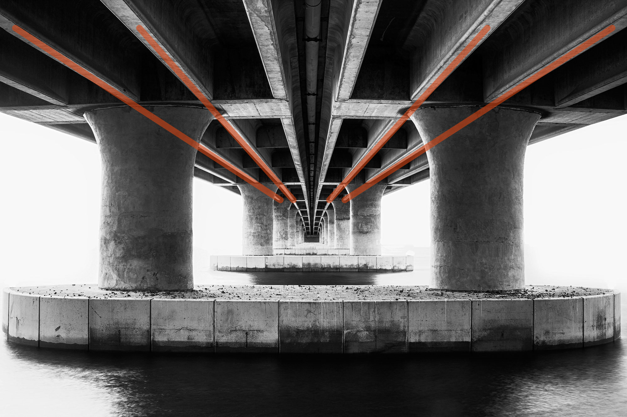 Concrete convergence photographed from underneath a bridge,  with added leading lines to show the compositional technique