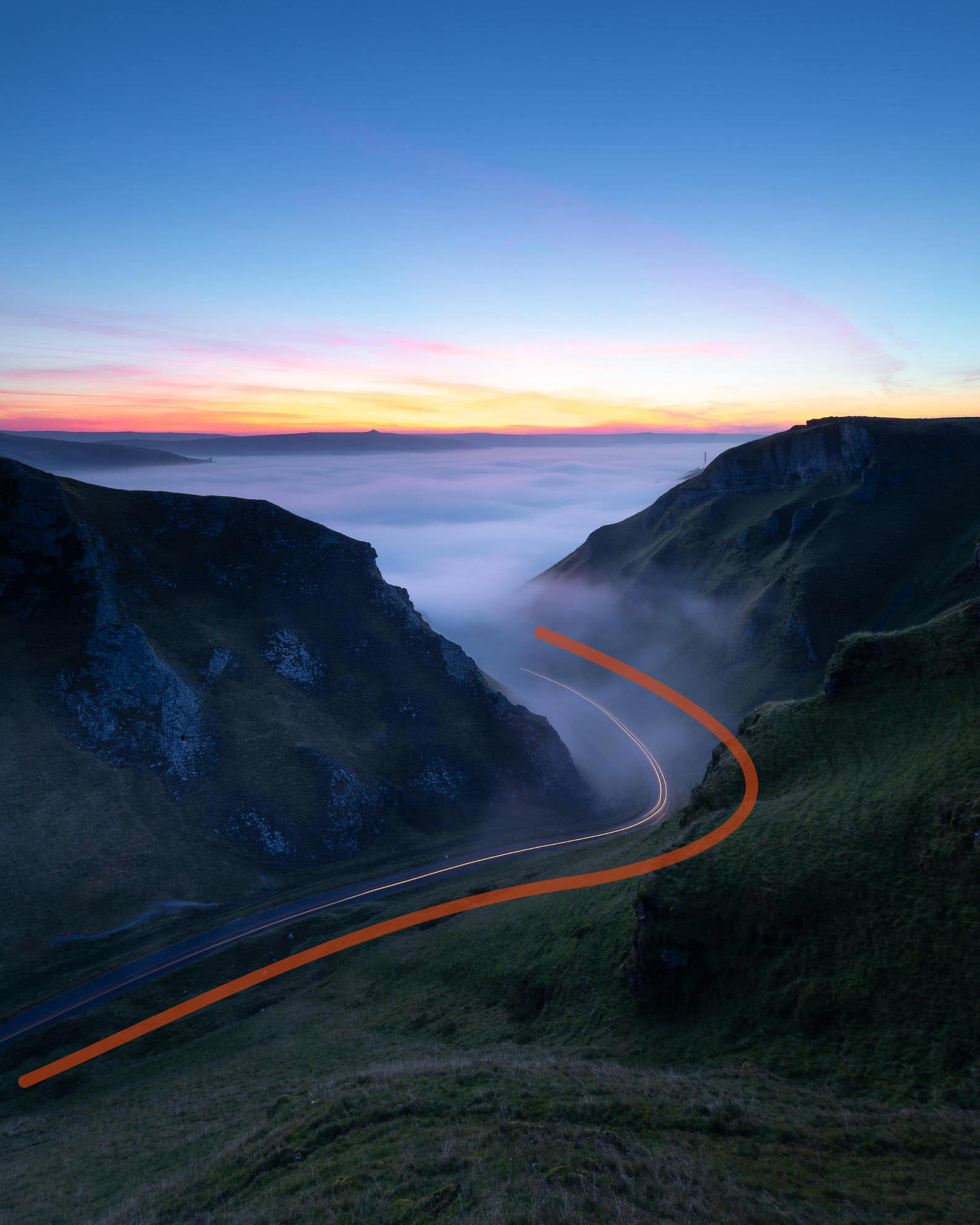 A colourful sunrise at Winnats Pass with a cloud inversion developing early on. A long exposure helped to capture the light trails of an emerging car, with an added leading line to show the compositional technique
