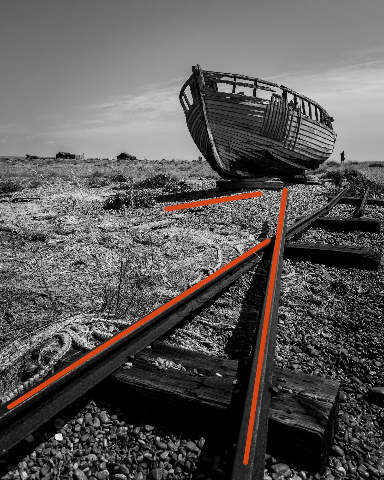 One of the many fishing boats left to rot on the beaches at Dungeness, with added leading lines to show compositional technique