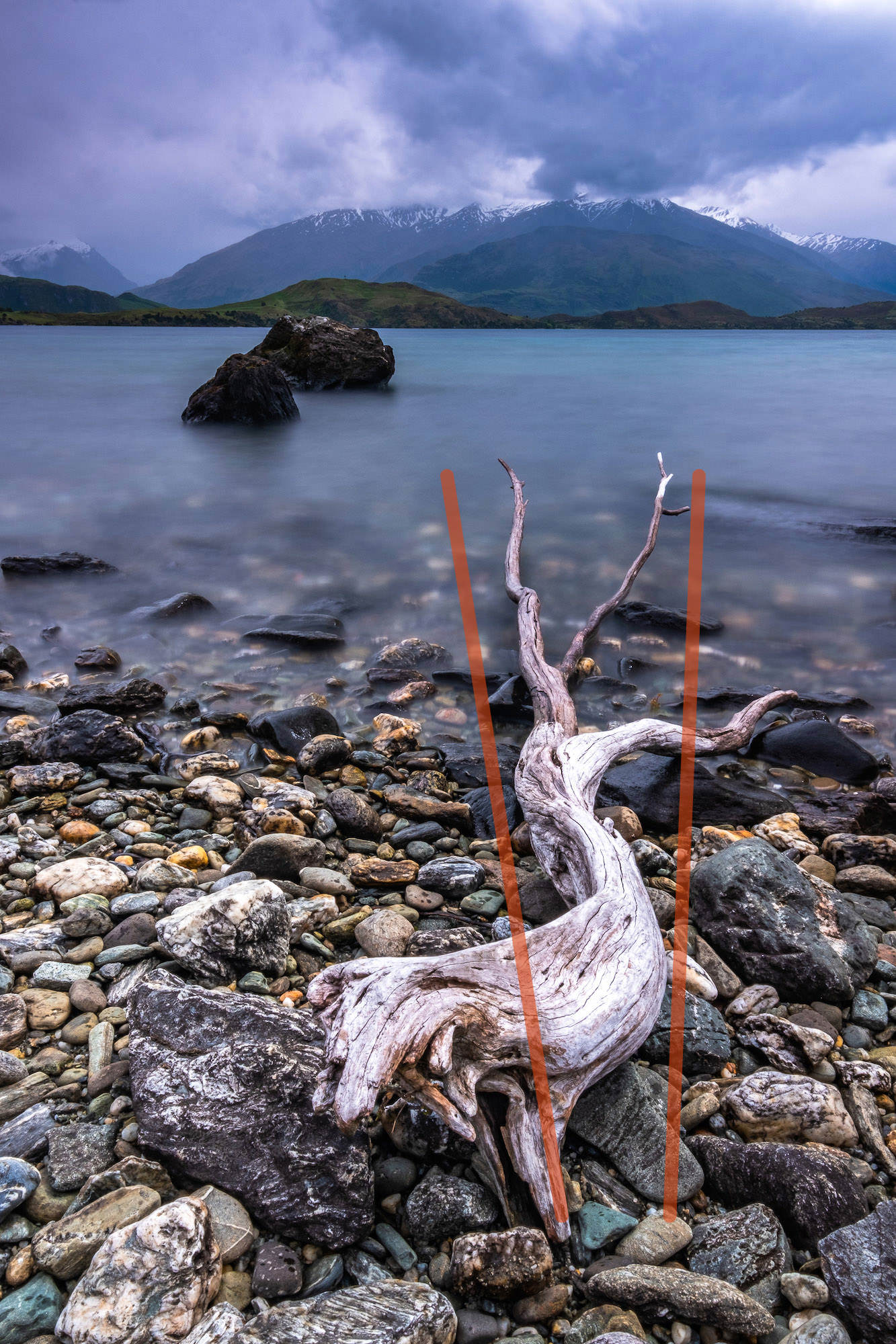 Washed up driftwood and pebbles make for a textured foreground as The Remakables are almost swallowed by low clouds; Queenstown, New Zealand. With added leading lines to show compositional technique.