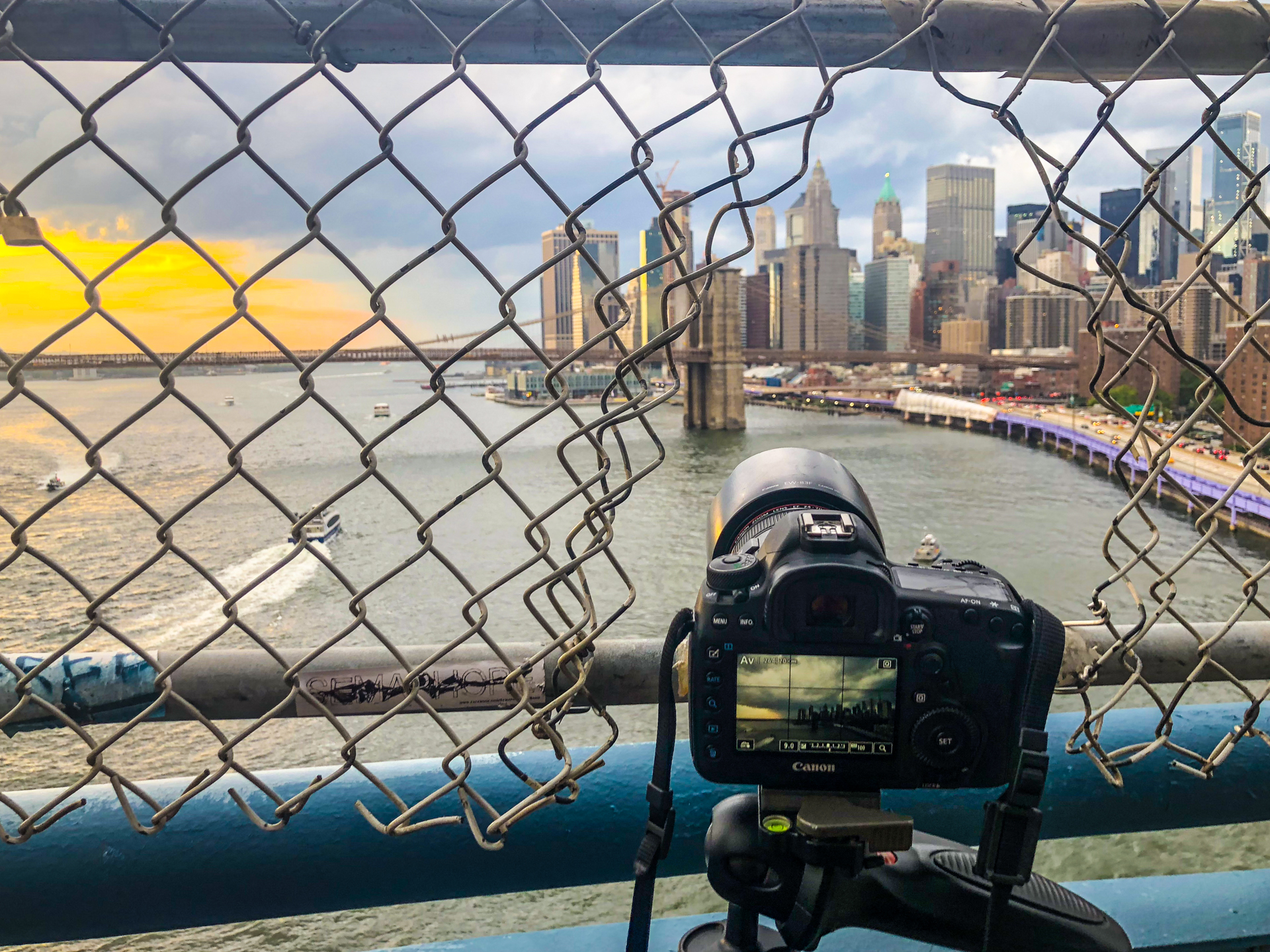A camera mounted on a tripod looking toward Lower Manhattan