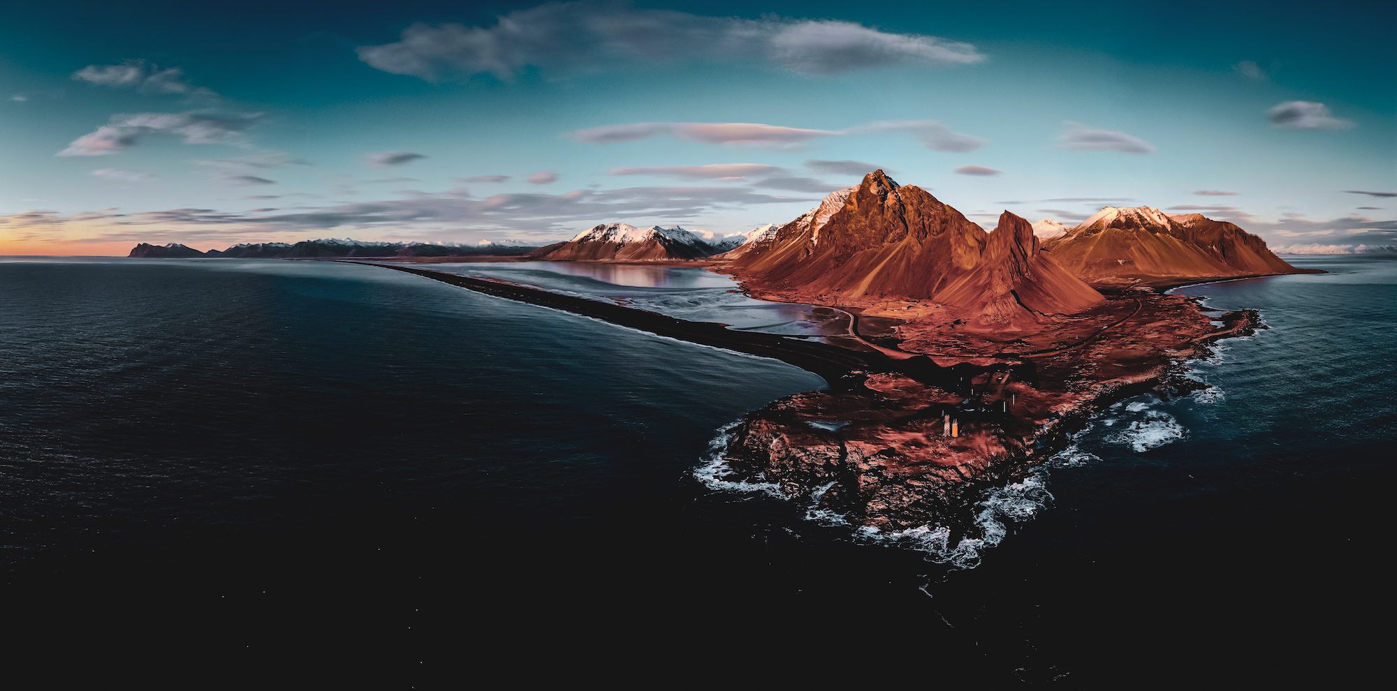 Full panorama of East Iceland coast with lighthouse, captured by drone during winter low sun