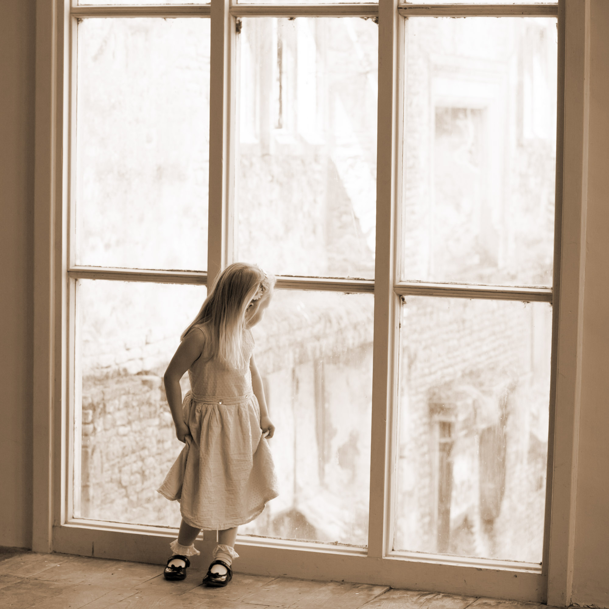 Little girl looking out of a large window