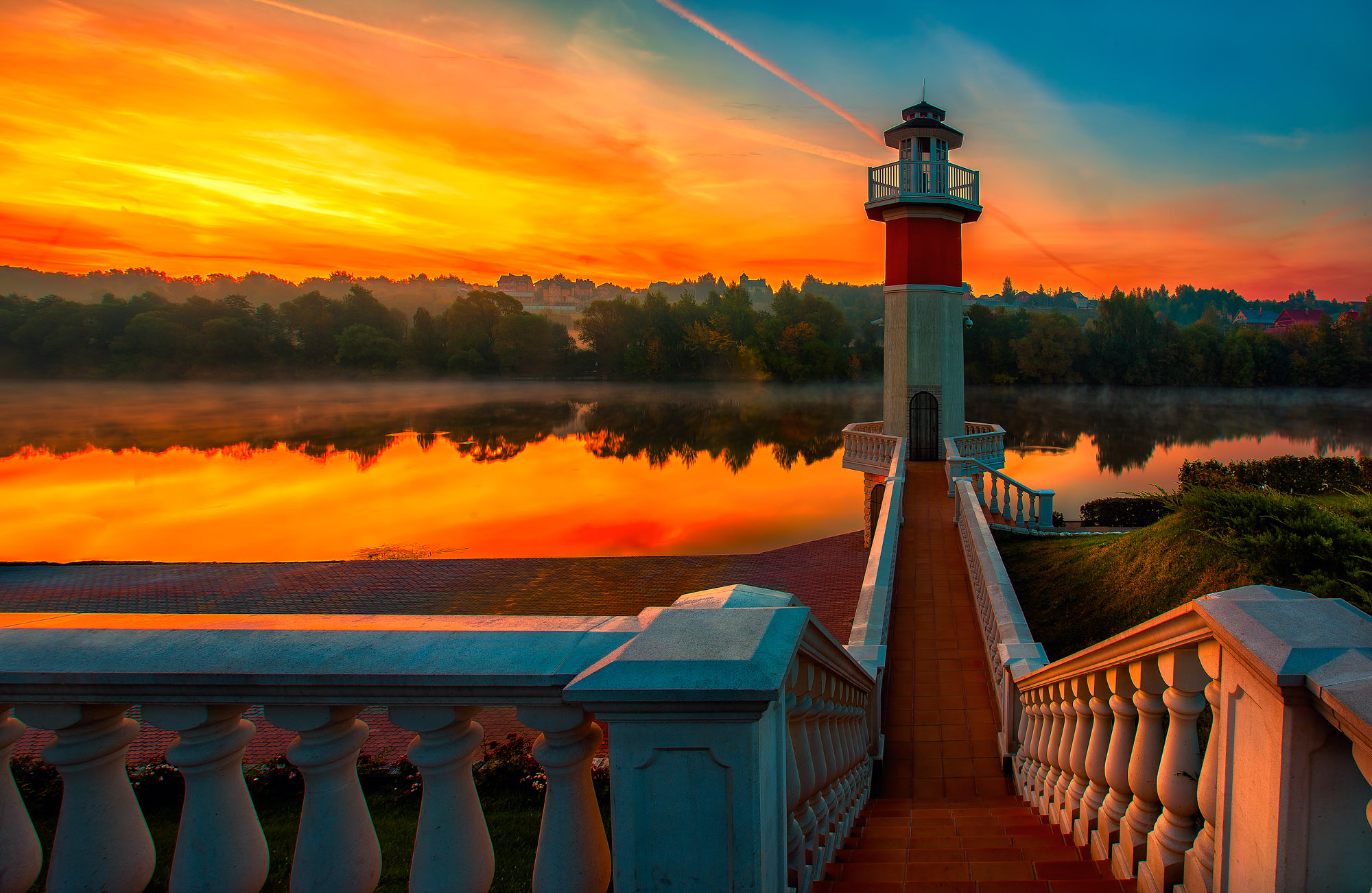 Sunrise at the river with a lighthouse in the foreground