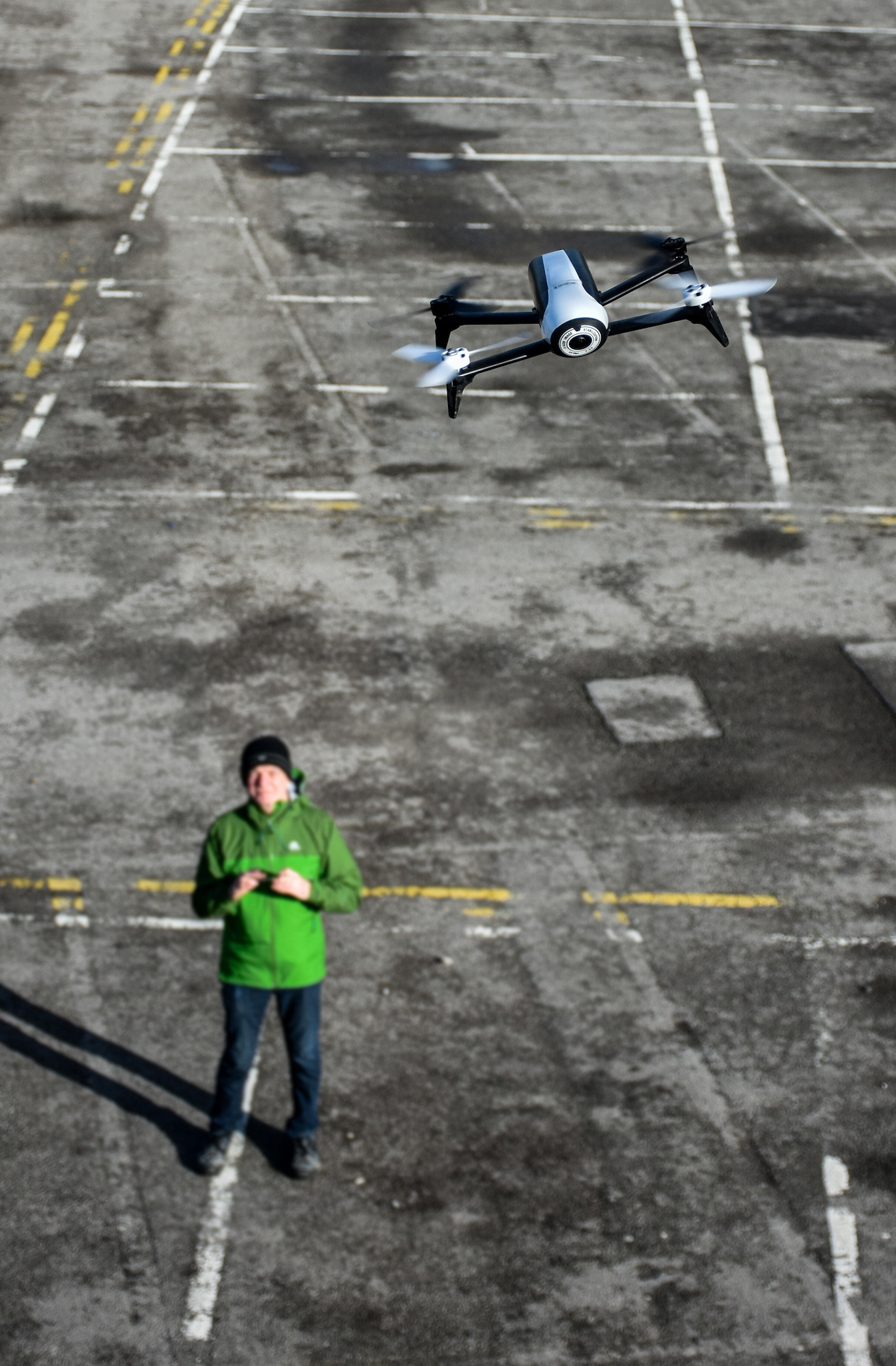 Man in a green coat flying a drone