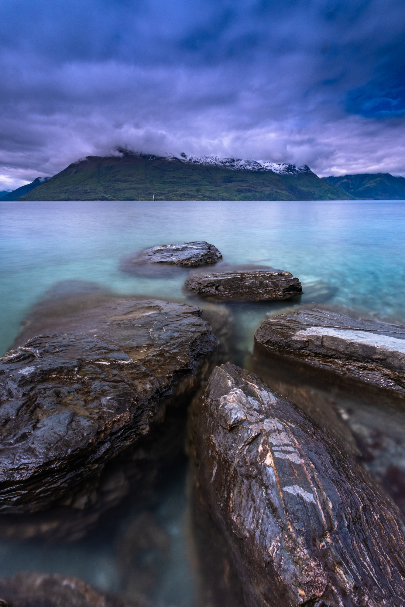 Vibrant blue water and storm clouds roll in over the Remarkables; Queenstown, New Zealand