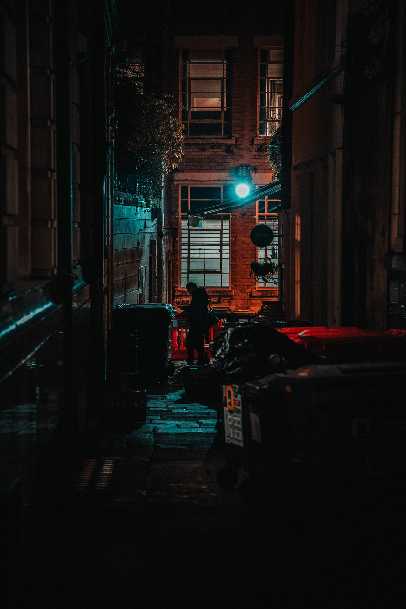 Moody scene of a person walking past an alley at night