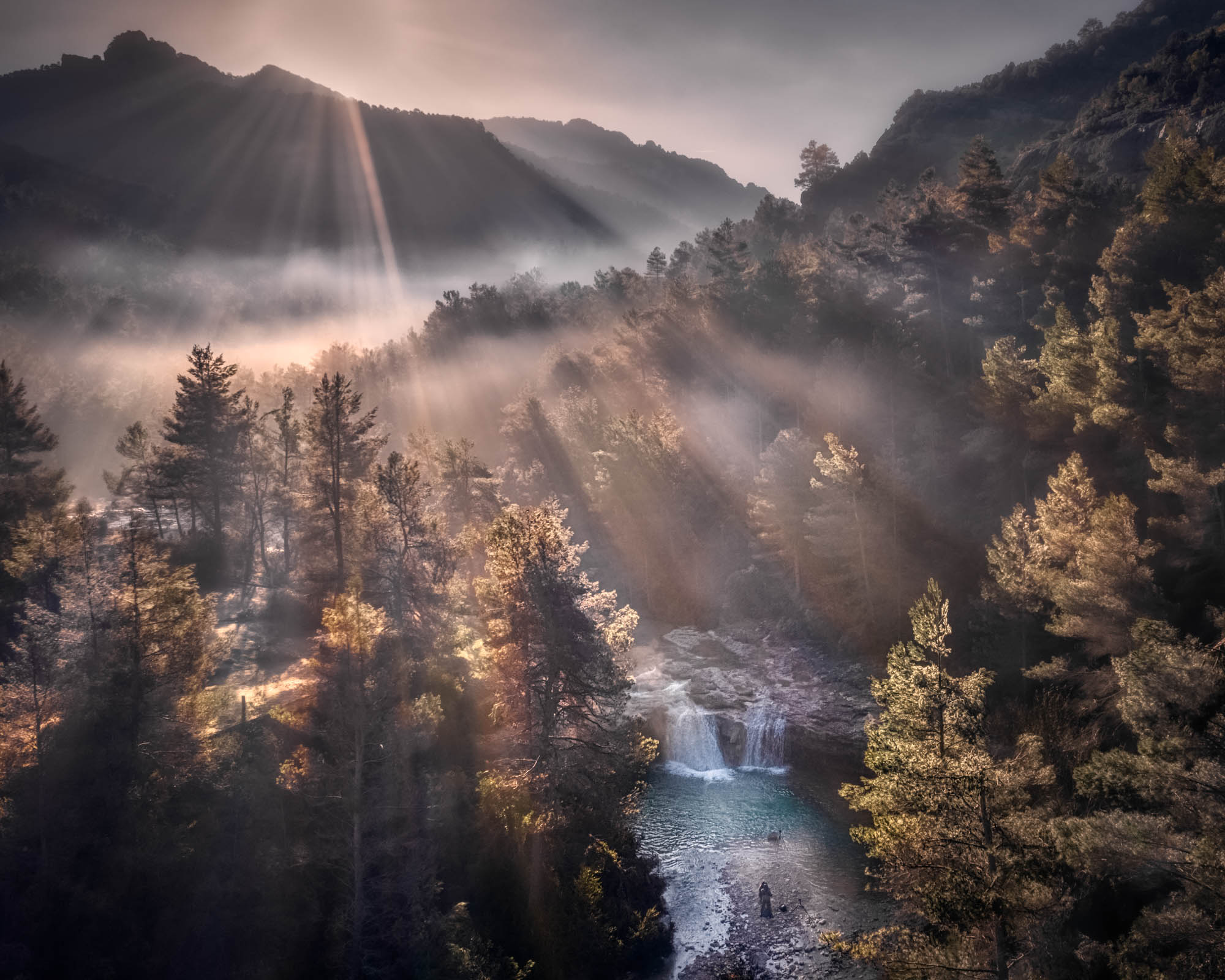Photo taken by drone of a waterfall in a foggy forest