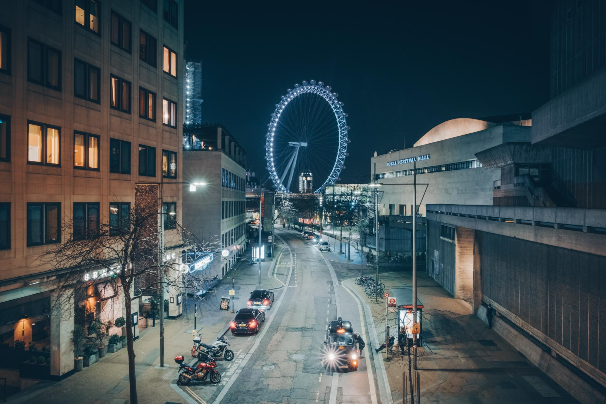 A taxi driver picking up in London while the London Eye shines bright in the background