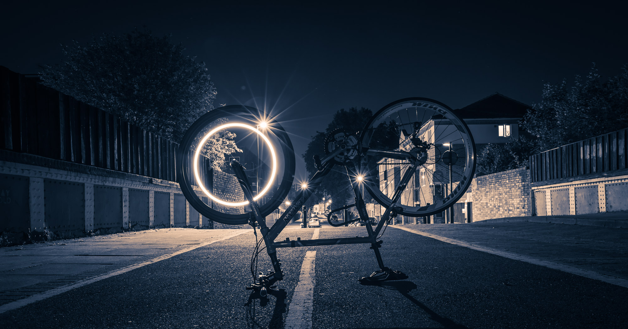 Long exposure of a light trail on the front wheel of a bike